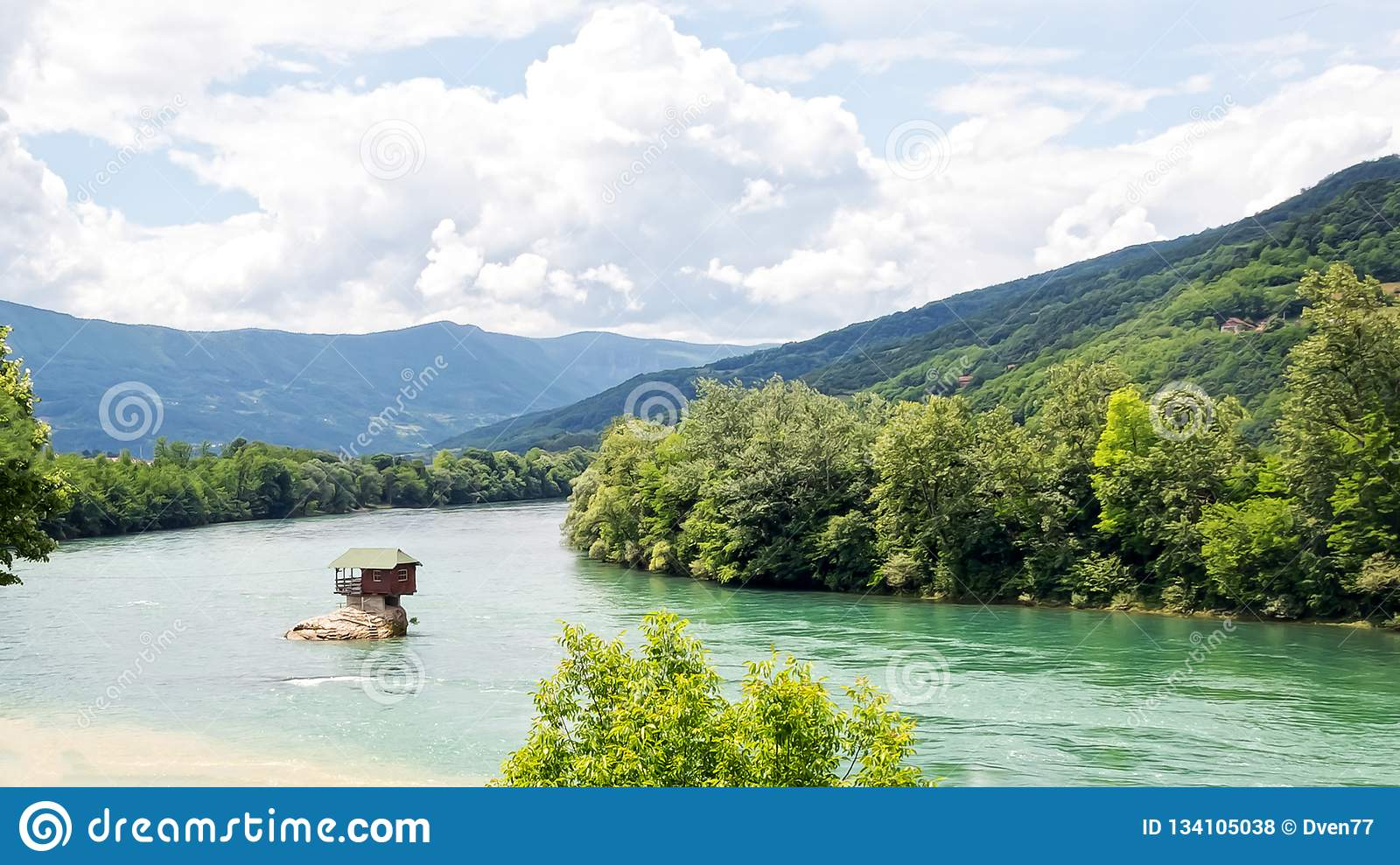 Lonely house on the river Drina in Bajina Basta. Cloudy sky and mountains on background. Serbia