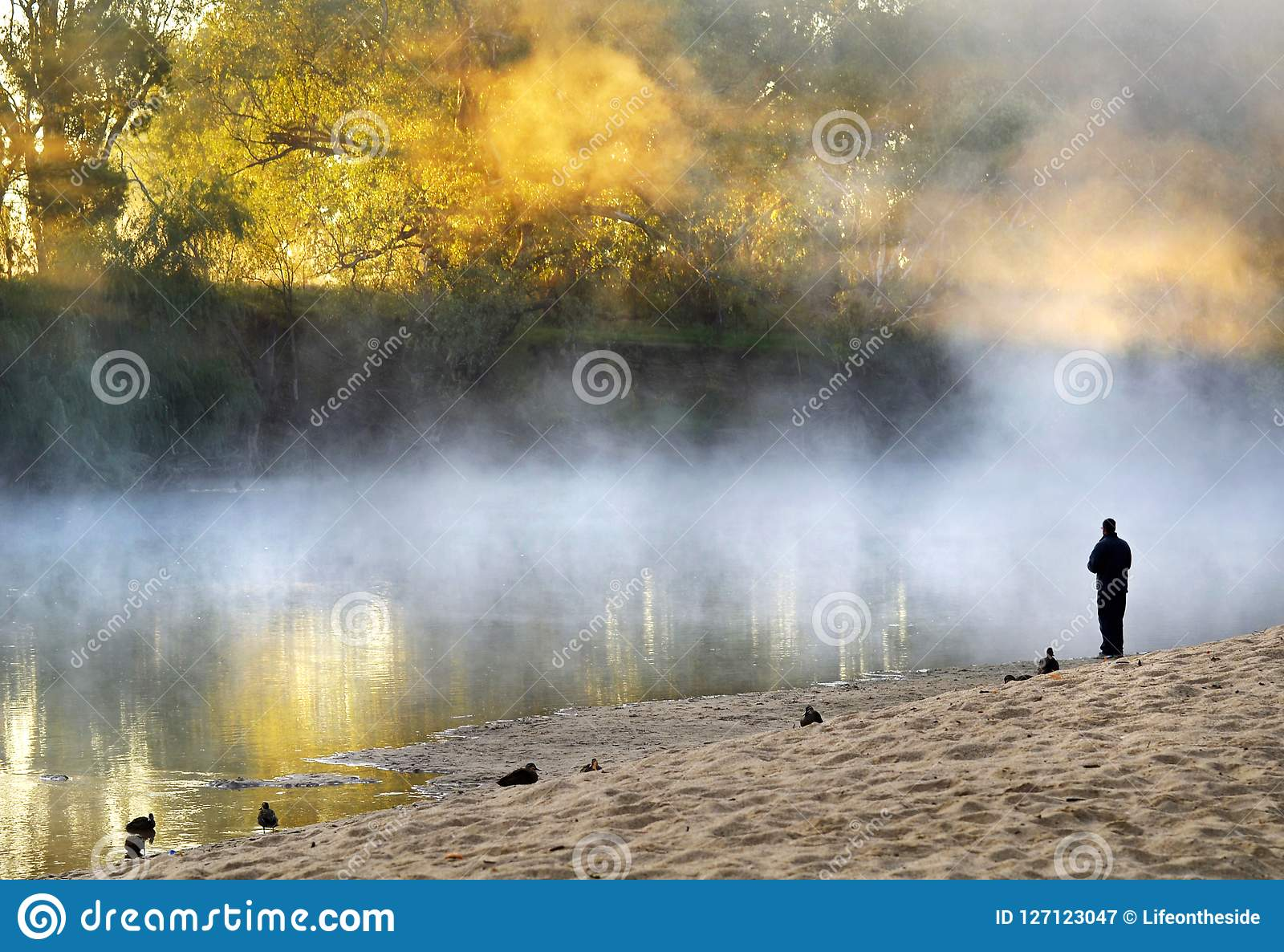 Lonely man standing soul searching on bank foggy misty river