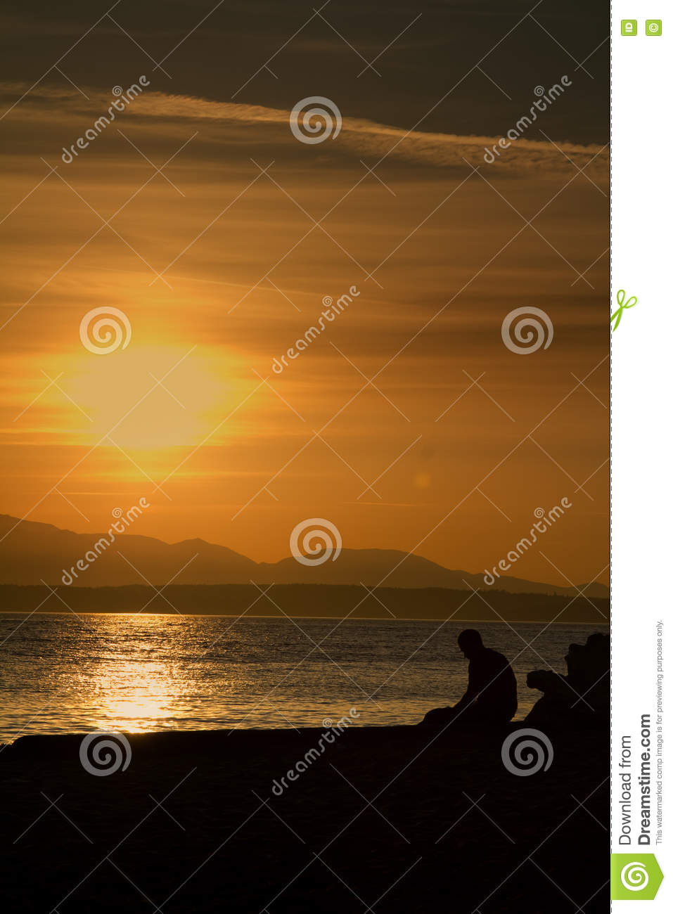 A Lonely Sad Man Sitting Alone At The Beach During Sunset. Shot At ...