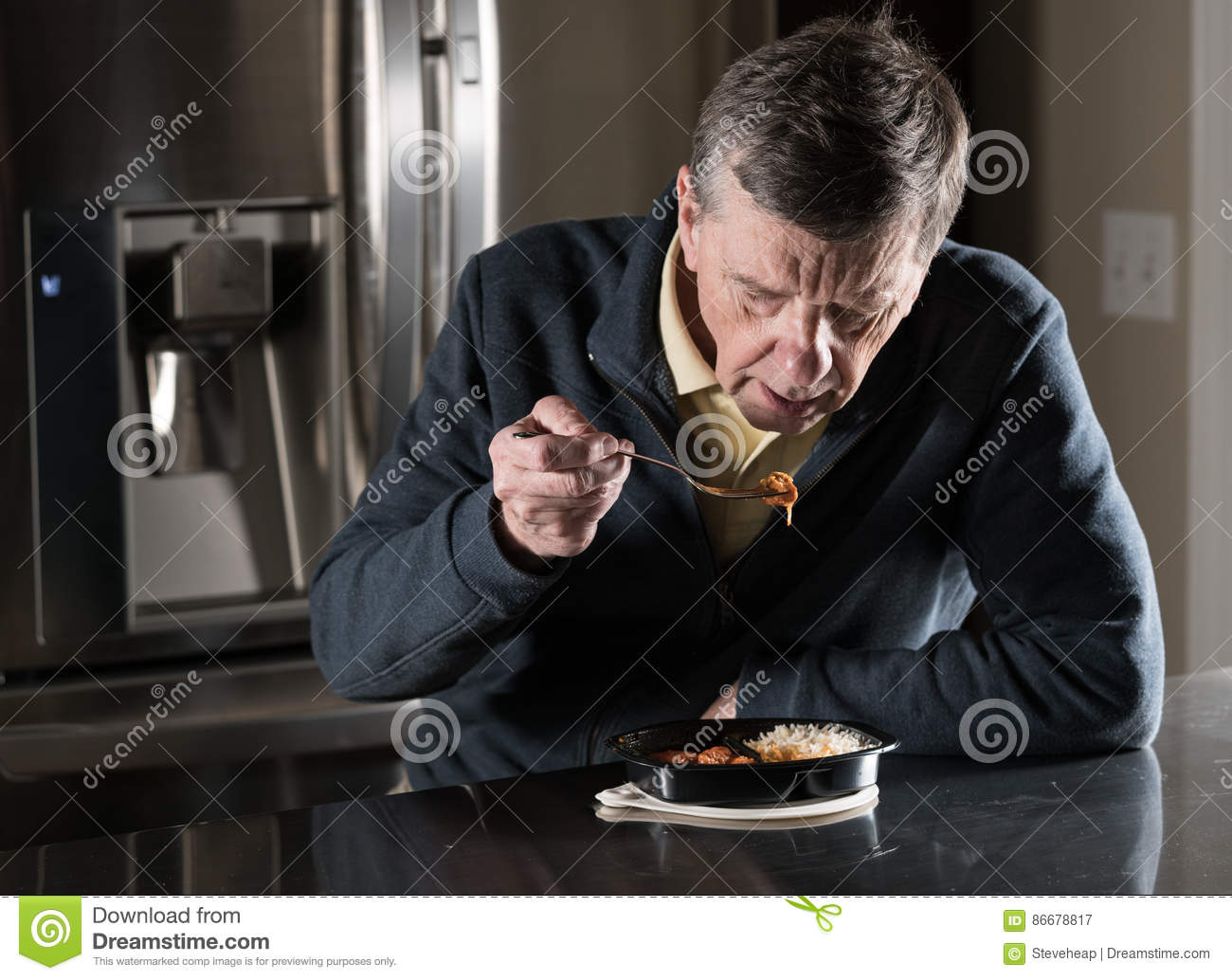 Lonely senior man eating ready meal at table