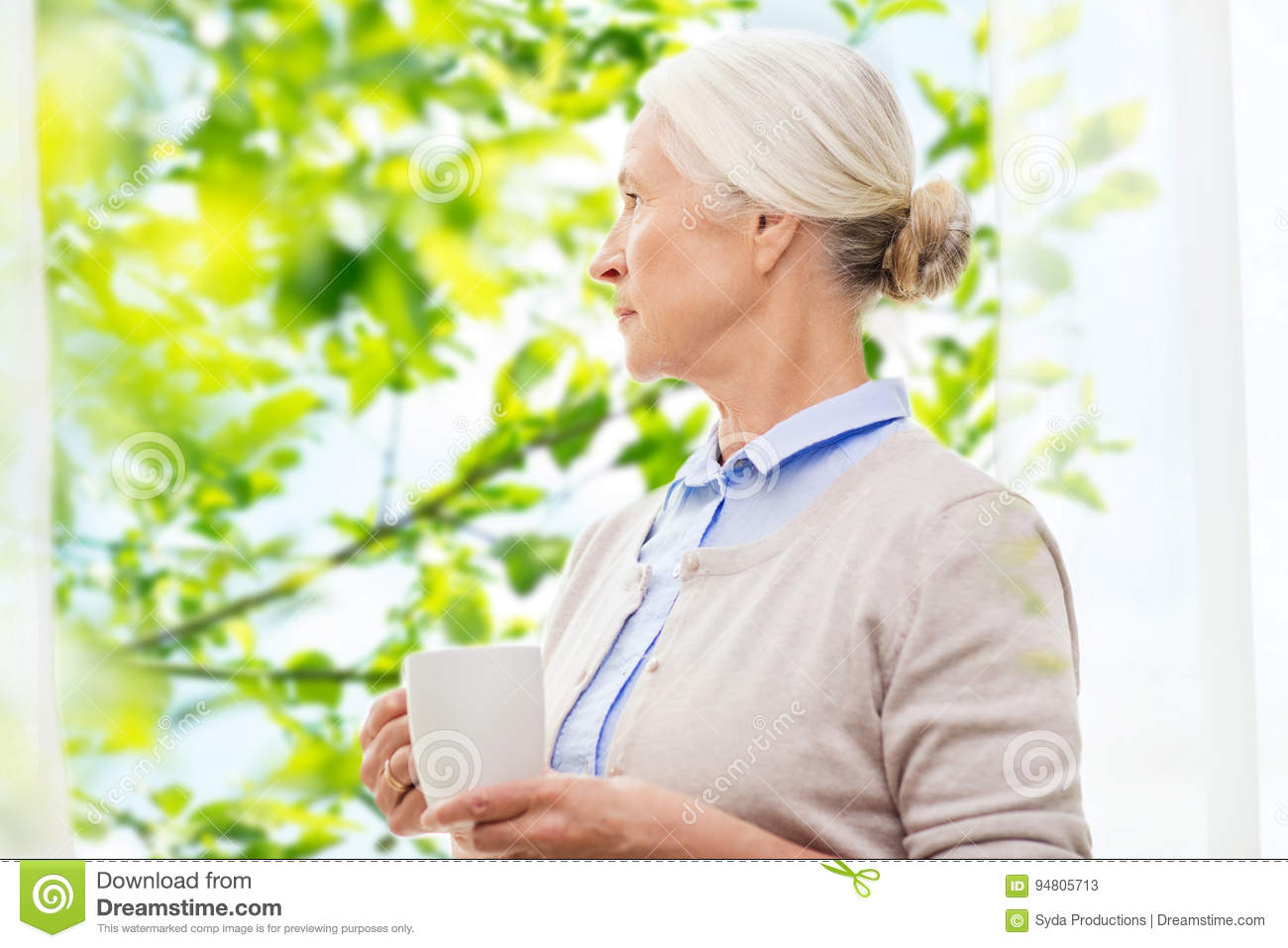 Lonely senior woman with cup of tea or coffee