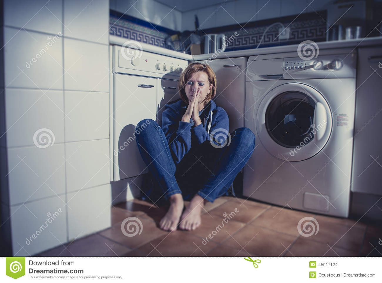 Lonely And Sick Woman Sitting On Kitchen Floor In Stress