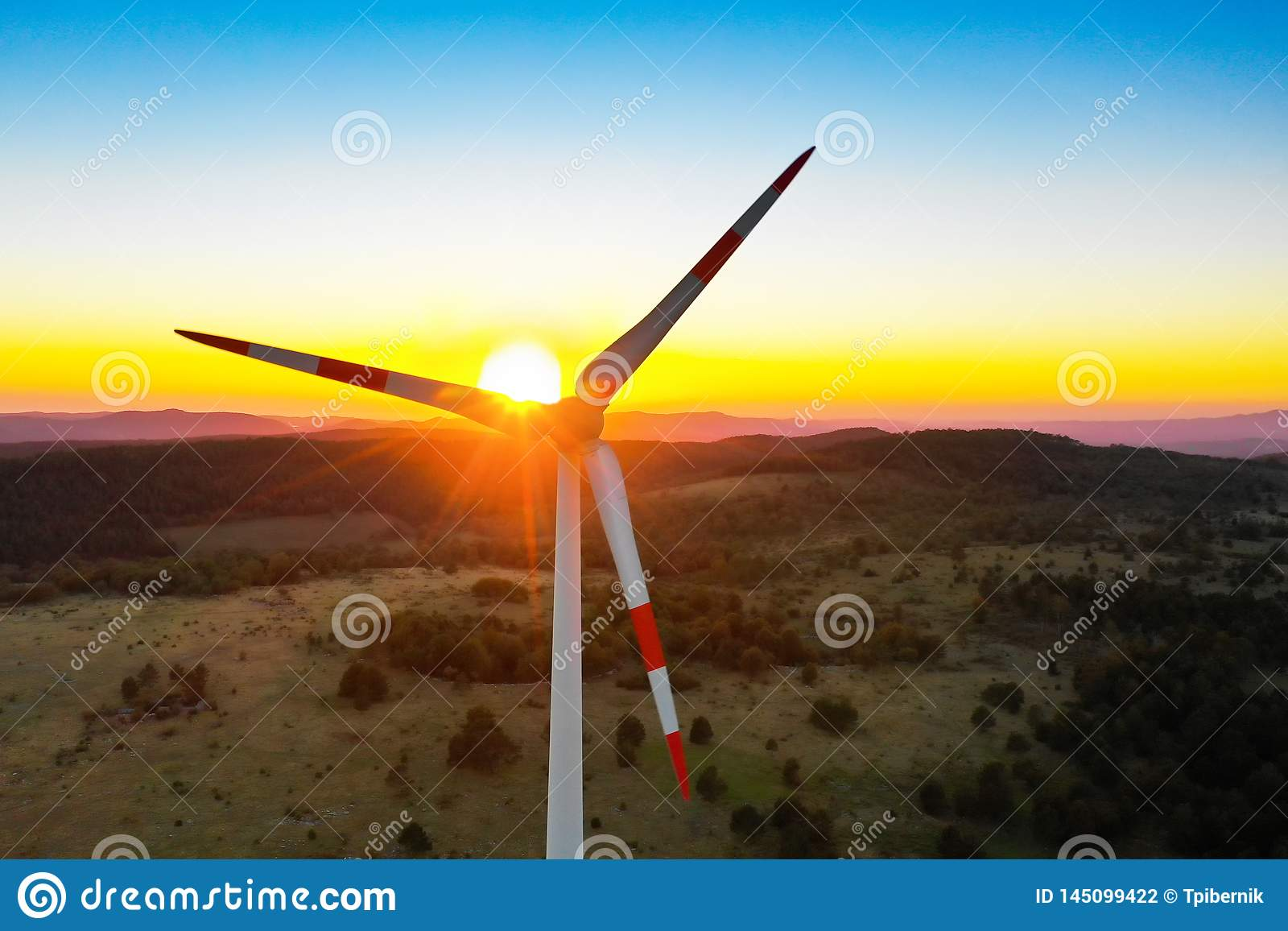 Lonely windmill turbine peacefully rotating blades through the wind in the beautiful sunset sky