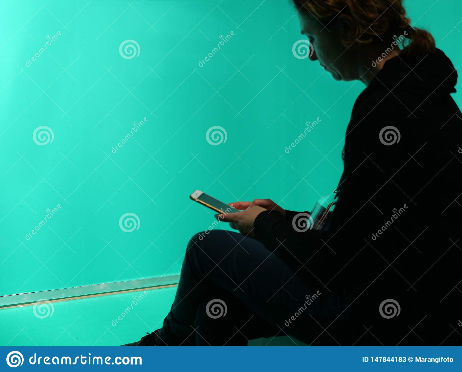 Lonely woman silhouette watching her smartphone isolated on blank green background