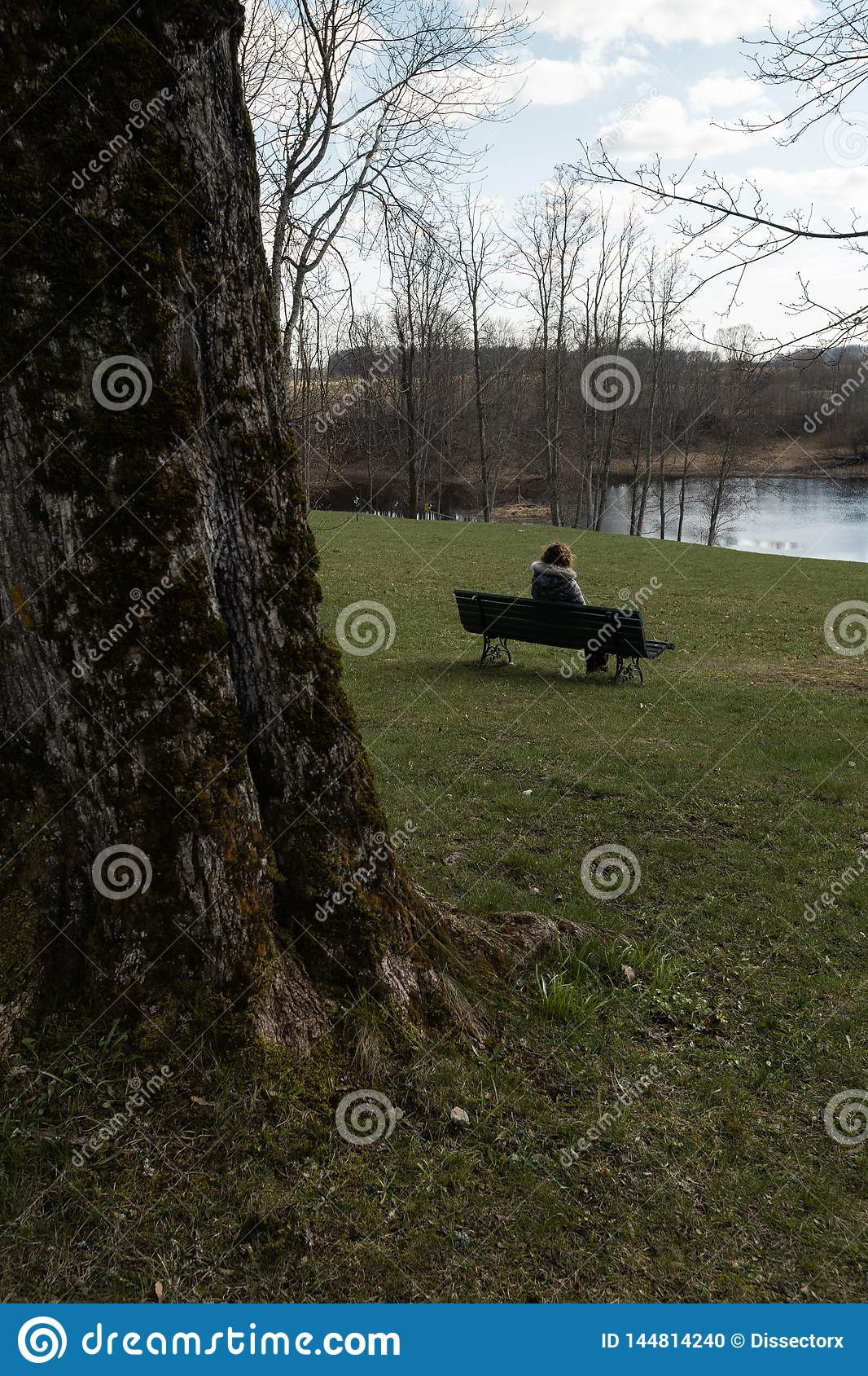 Lonely woman sitting on a bench in a park thinking about life looking at the horizon -Liepupes Muiza manor in beautiful