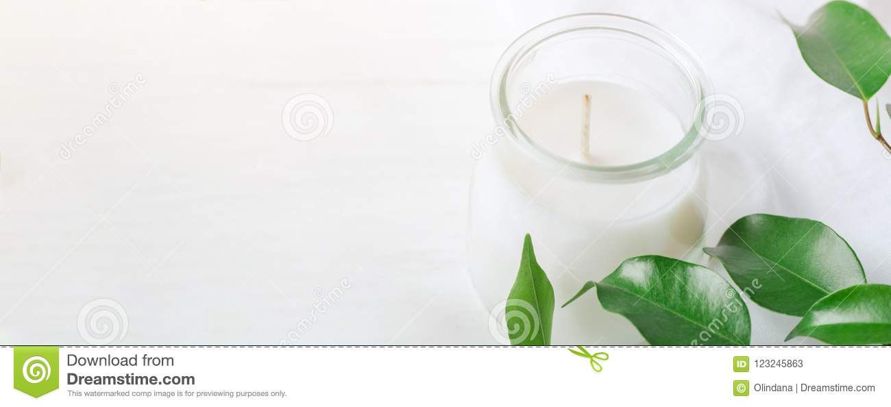 Long Banner for Organic Cosmetics Wellness White Candle in Glass Jar Fresh Tree Branches with Green Leaves on Wood Background. Spa