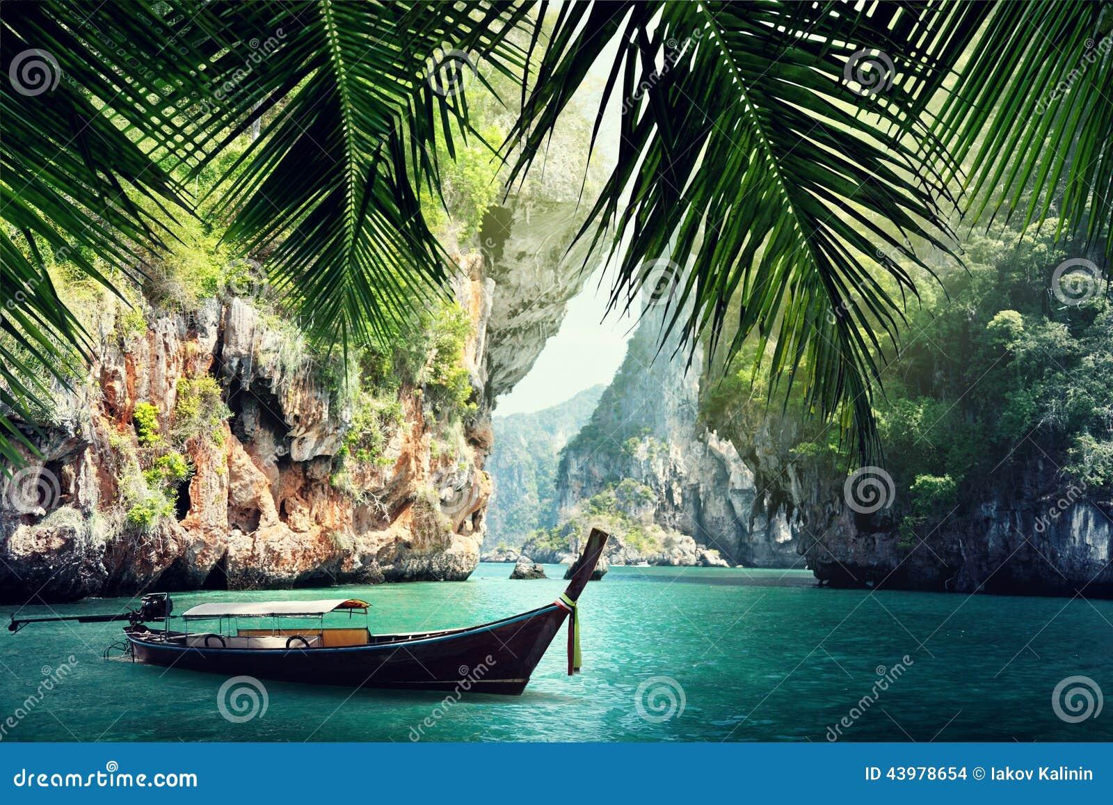 Long boat and rocks on beach in Krabi