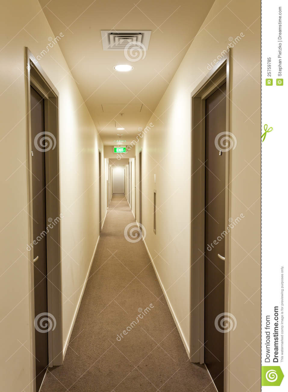 Long Corridor With Hotel Room Doors And Exit Sign Royalty