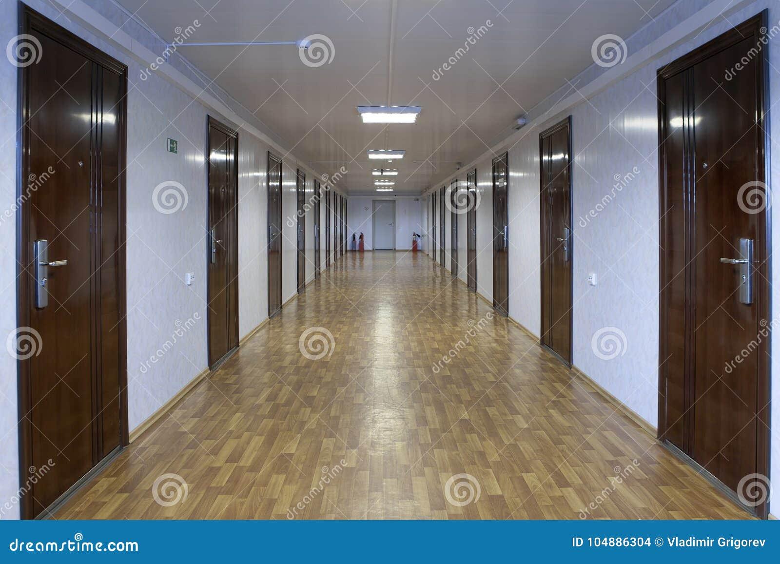 Long couloir de bureau avec beaucoup de portes de bois rouge foncé