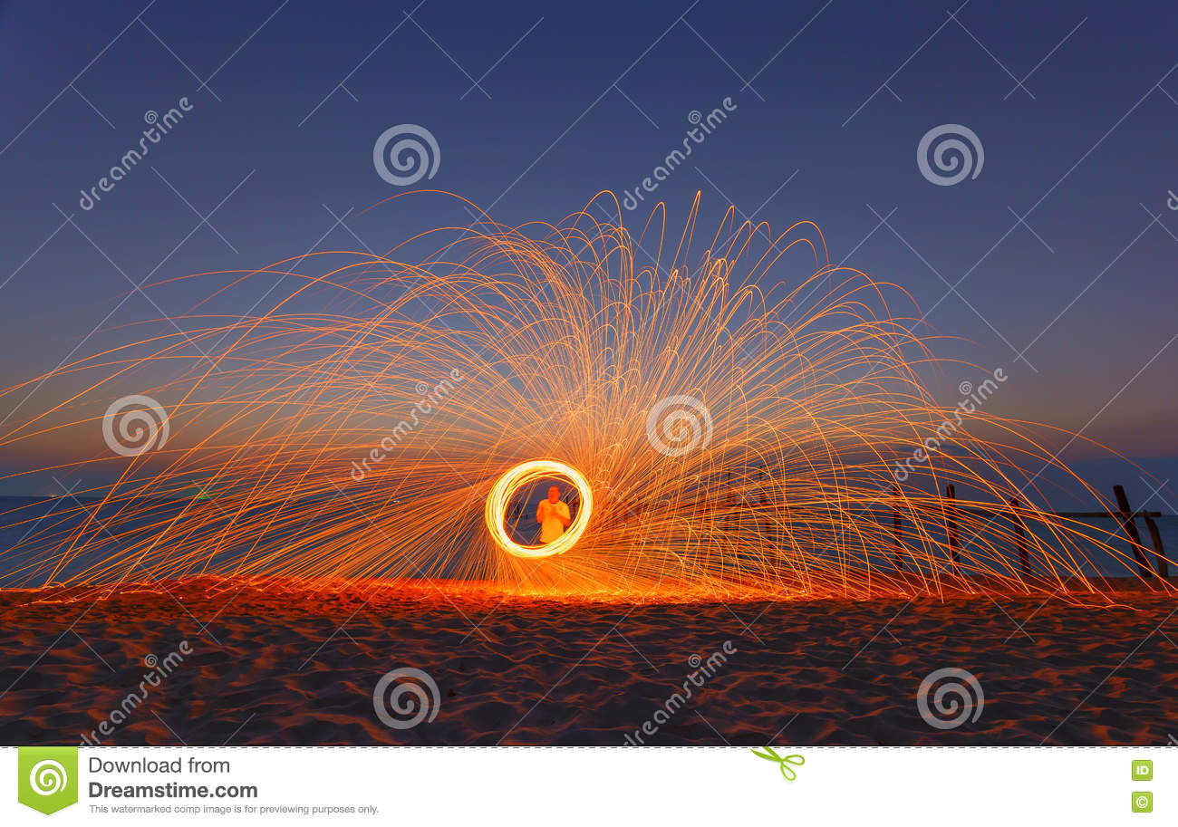 Long exposure of burning steel wool being spun into a sphere on