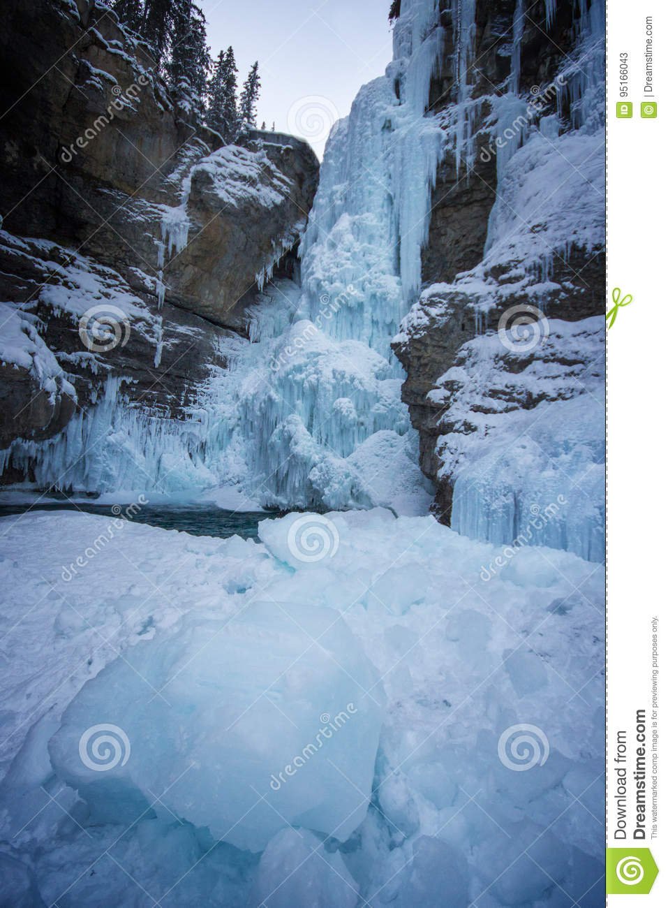 Long frozen waterfall with icy walls of canyon and big piece of ice in front, Johnston canyon, Banff national park, Canada