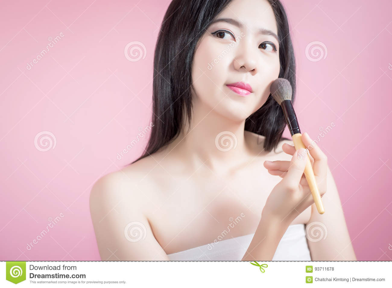 Long hair asian young beautiful woman applying cosmetic powder brush on smooth face over pink background. natural makeup.