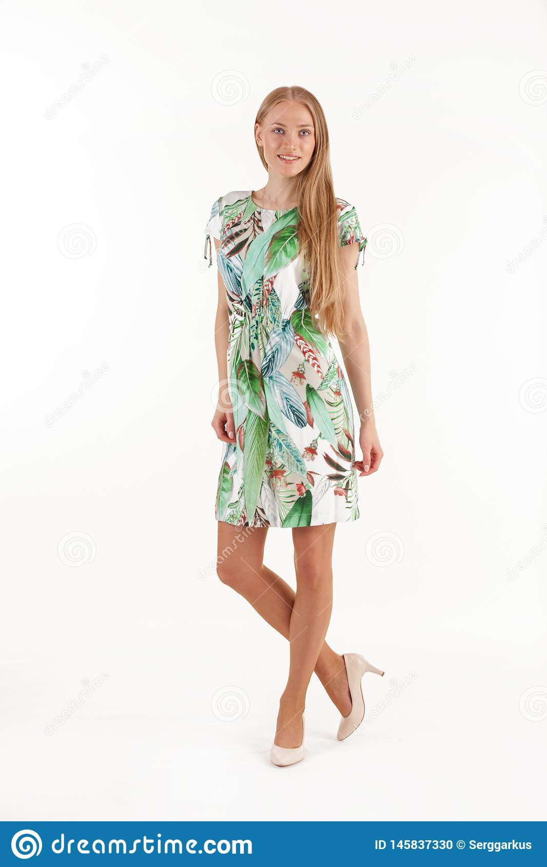 Beautiful young blonde woman in white dress with tropical print isolated on white background