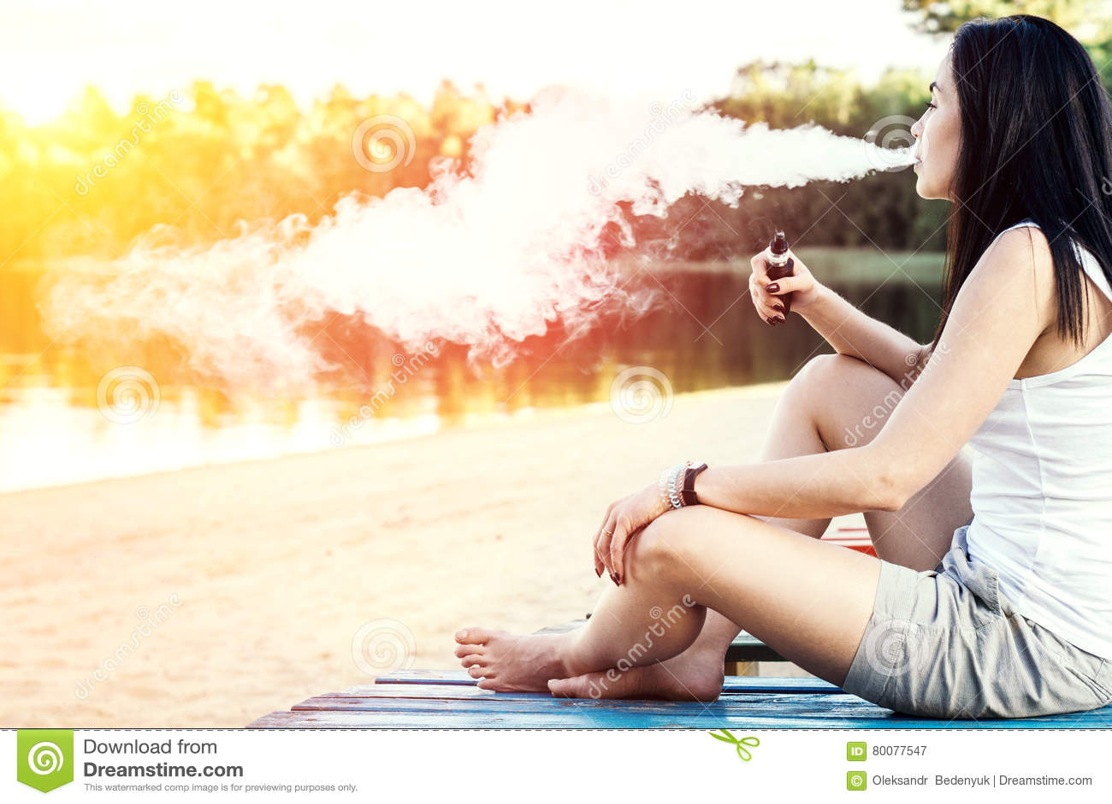 Long hair brunette girl smoking electronic cigarette on the beach