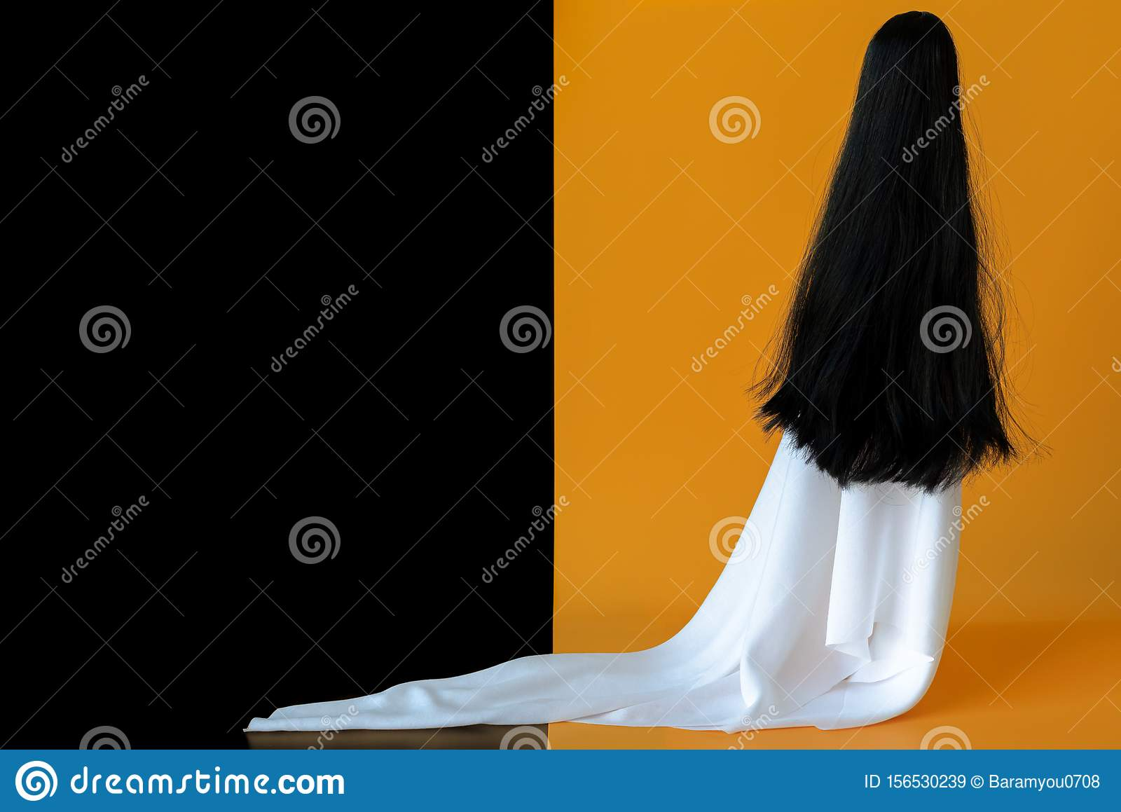 Long hair female ghost with white sheet costume with black and orange background. Minimal Halloween scary concept