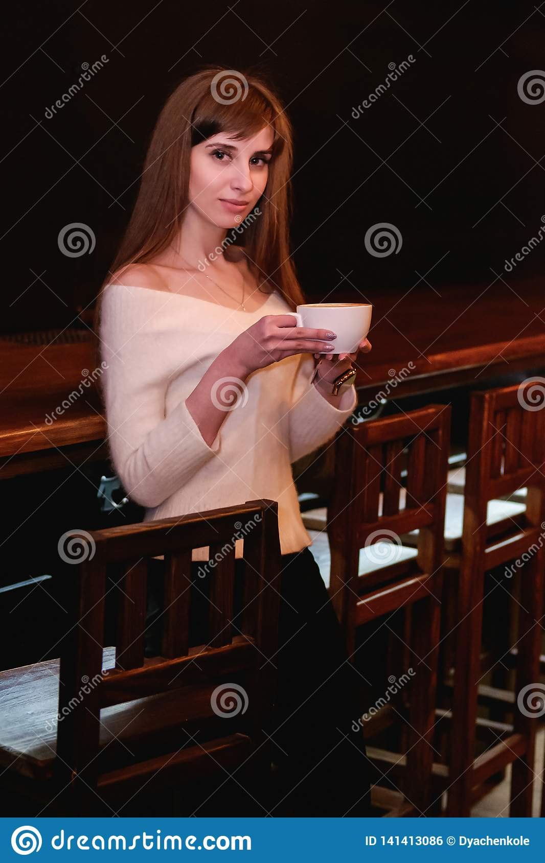 Long-haired beautiful girl in a white sweater is standing in a coffee shop at a wooden table with a cup, a lonely girl