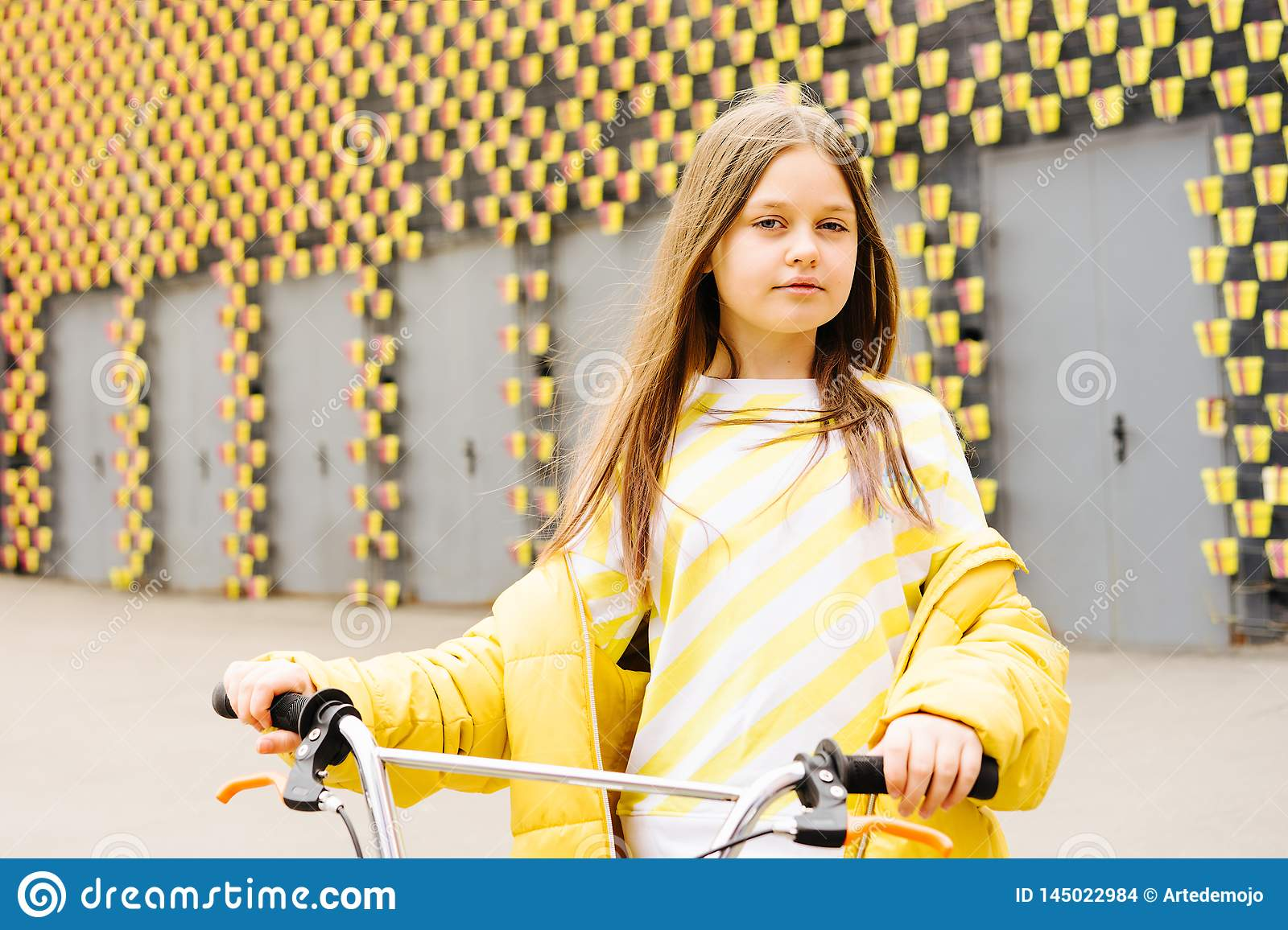 Long-haired blonde girl in a yellow sweater and yellow jacket