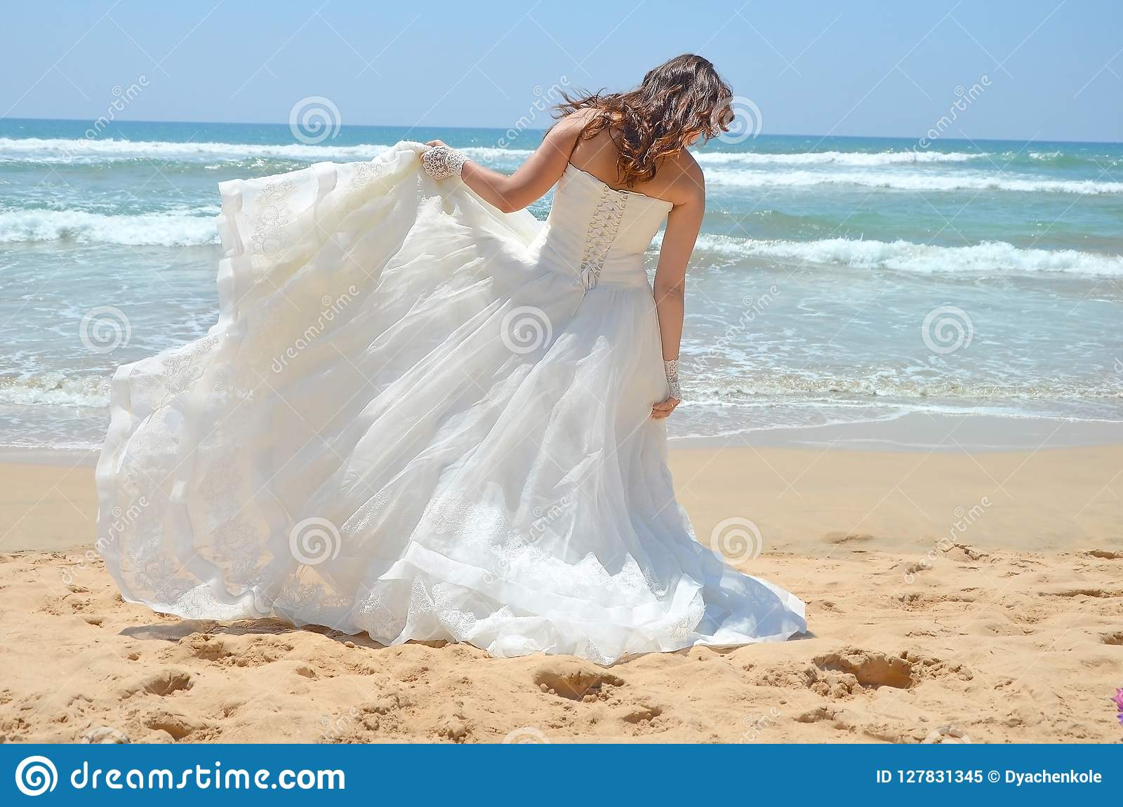 Long-haired brunette bride straightens her dress standing on the sand, the beach on the Indian Ocean. Wedding and honeymoon