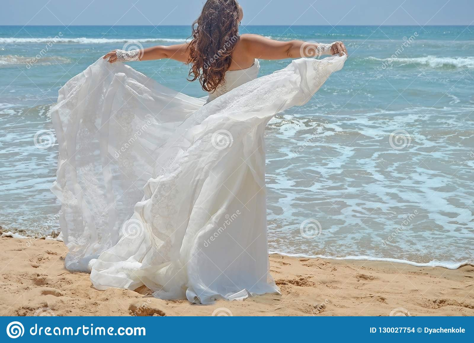 Long-haired brunette bride straightens her dress standing on the sand, girl looks up at the sky on beach on the Indian Ocean. Wedd
