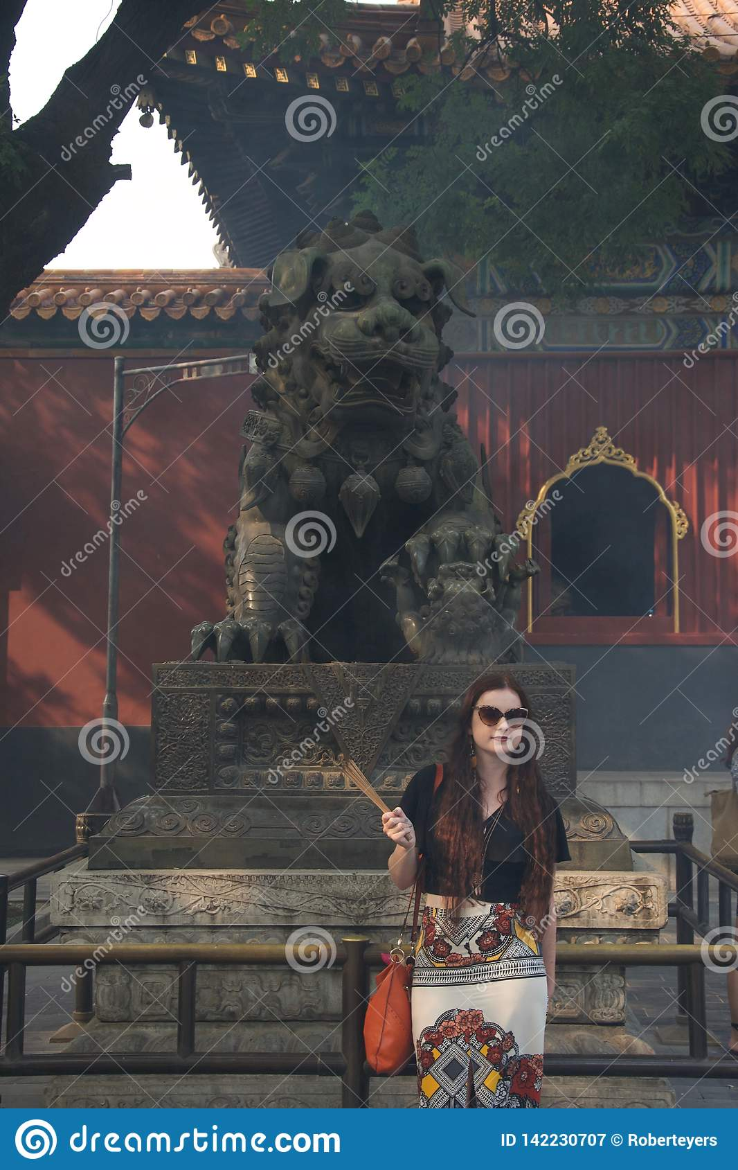 Fashionable female caucasian tourist with incense in Chinese temple in front of statute