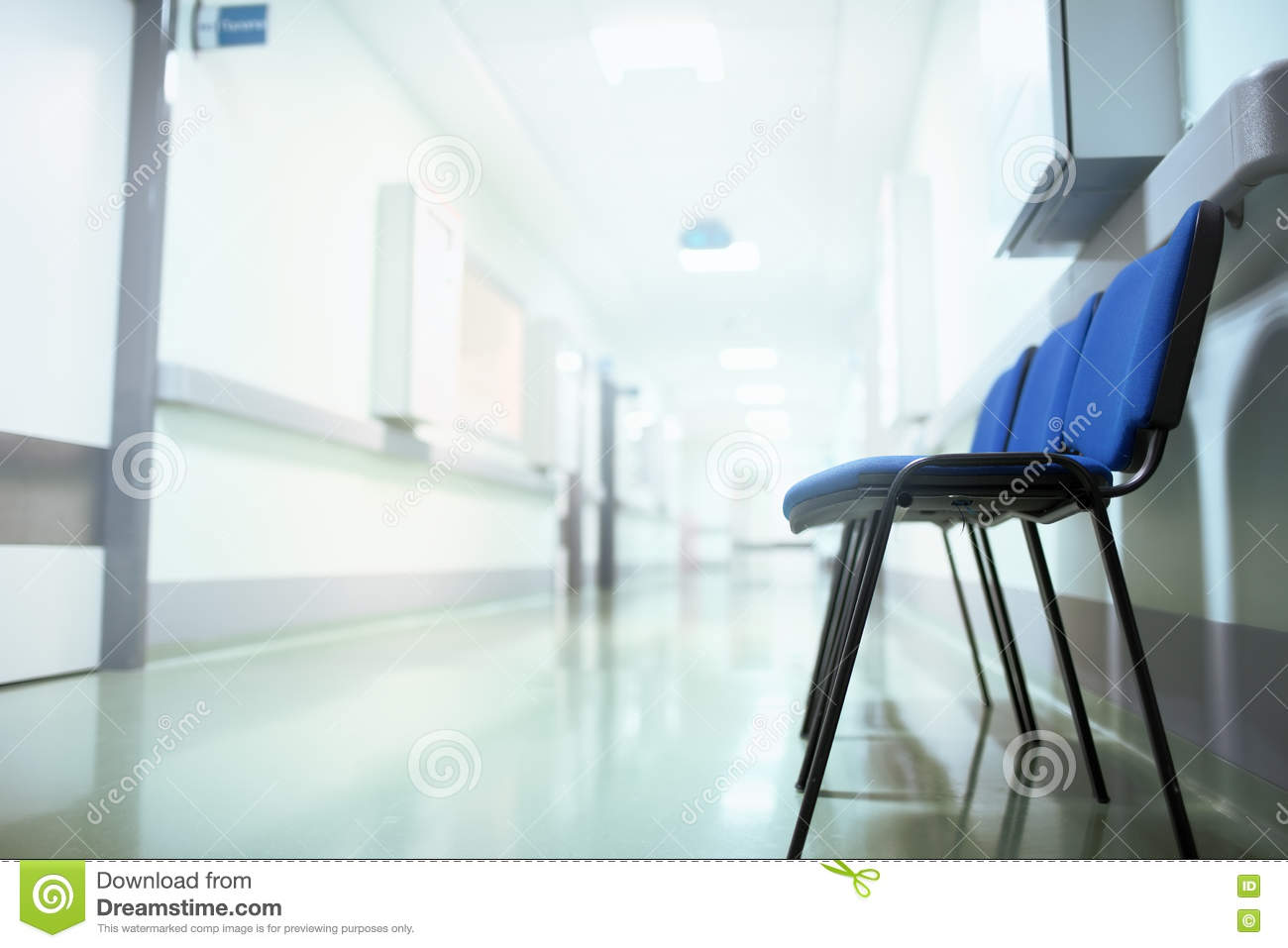 Long hospital hallway with vacant chairs