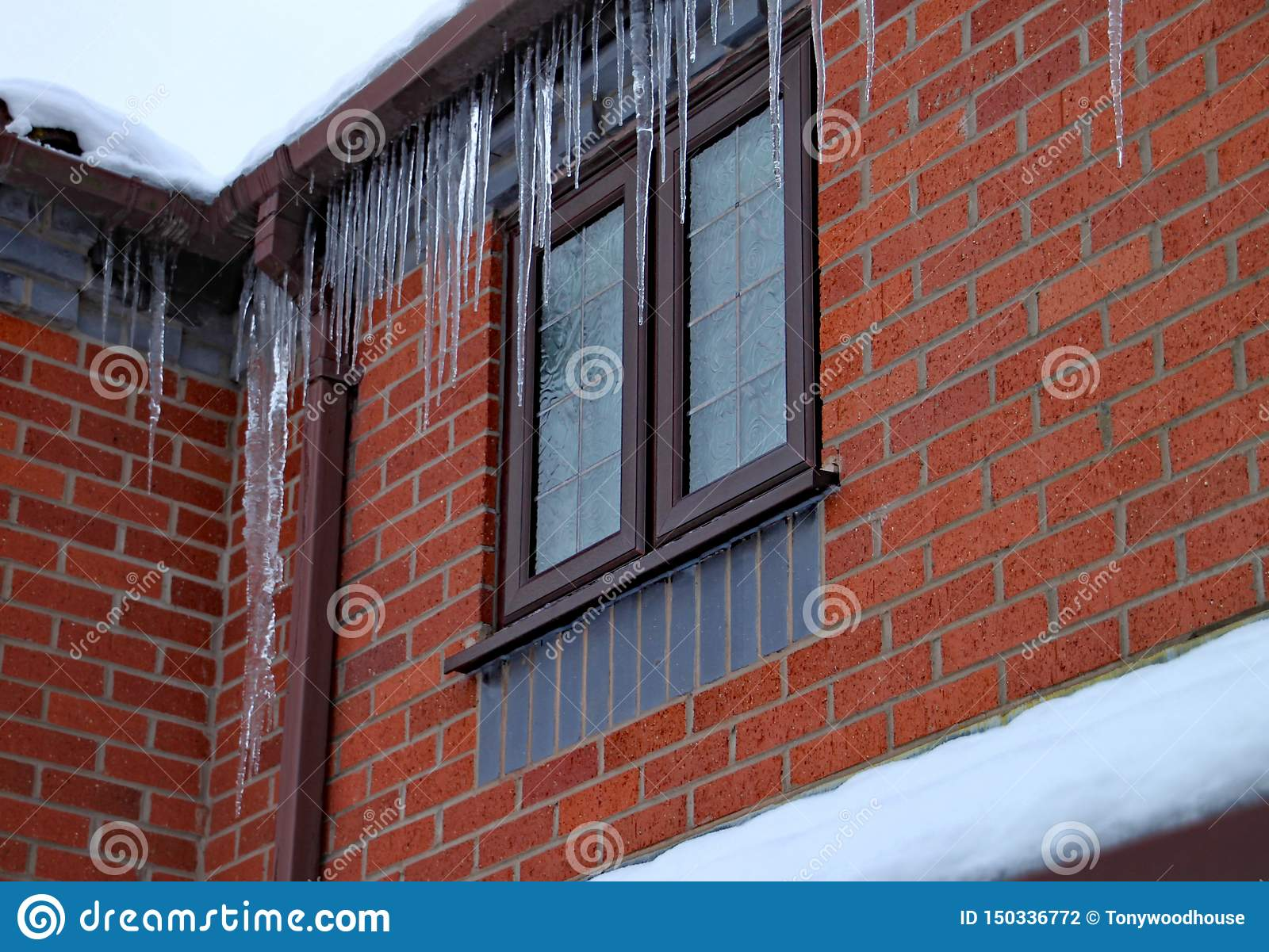 Long Icicles Hang From The Gutter Of A House The Roof Is