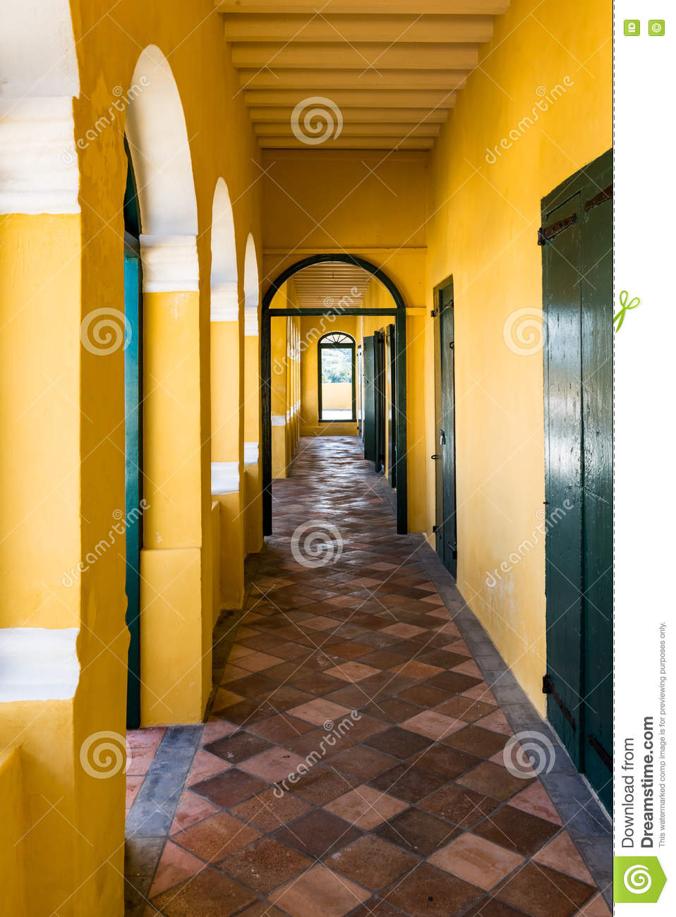 Long narrow passageway in old fort with yellow walls and brown c