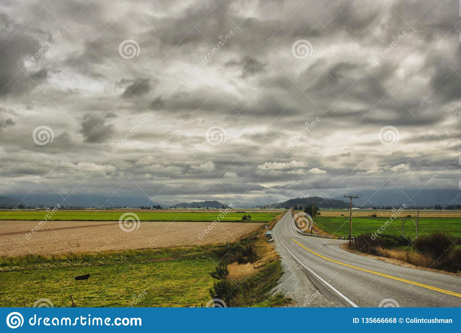 Long road cuts across valley, under looming clouds