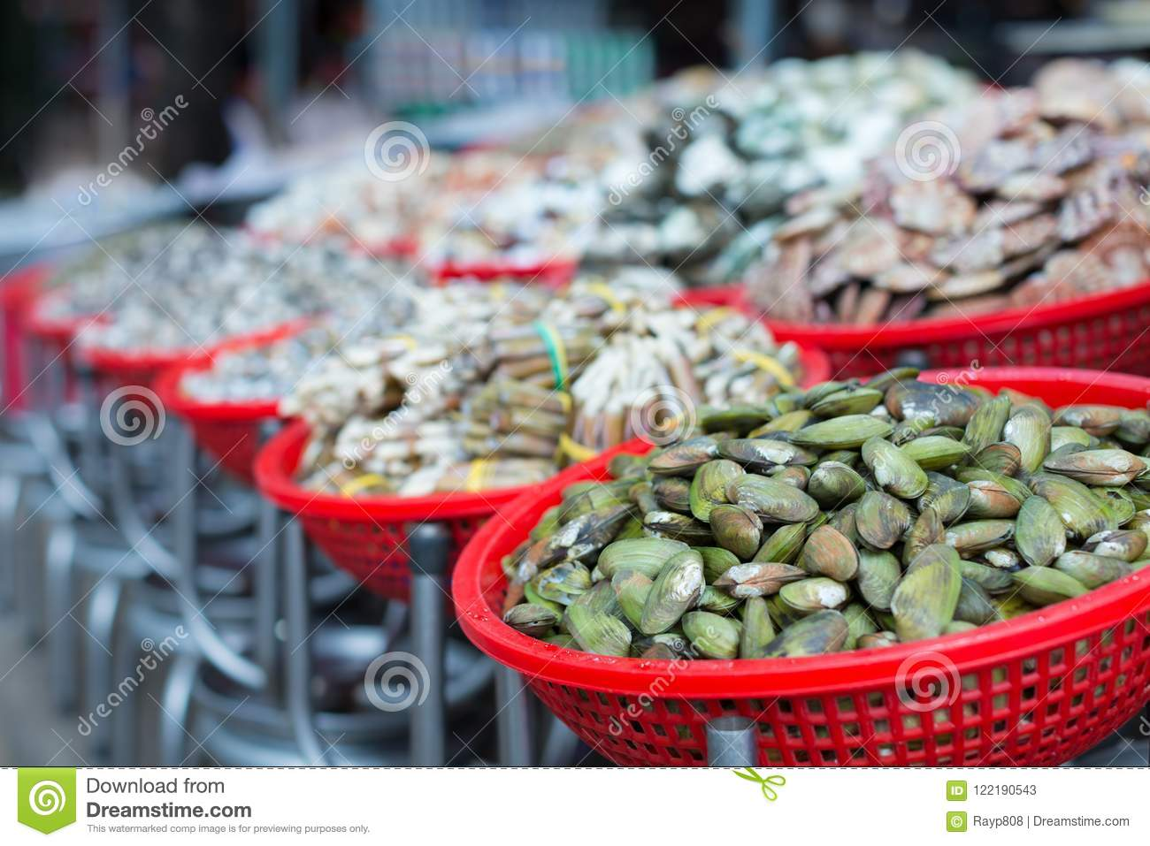 A long row of baskets full of mussels, clams, and a large assortment of shellfish