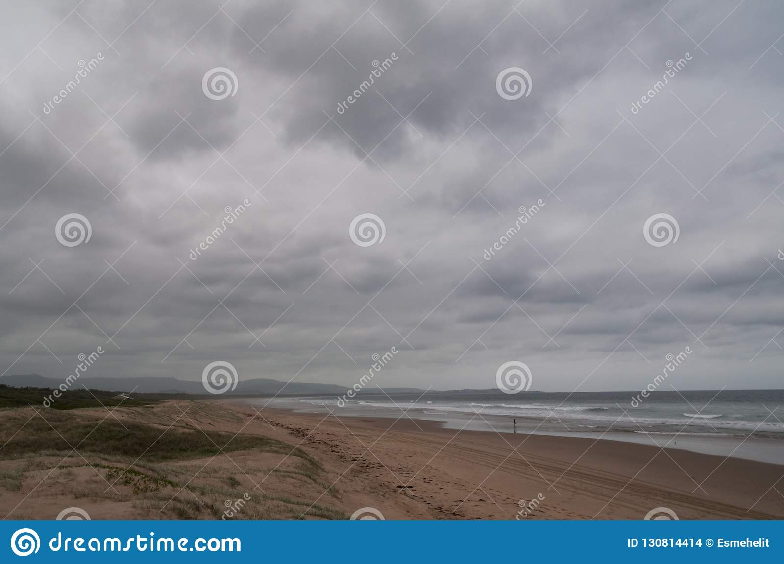Long sandy beach coastline with low storm clouds