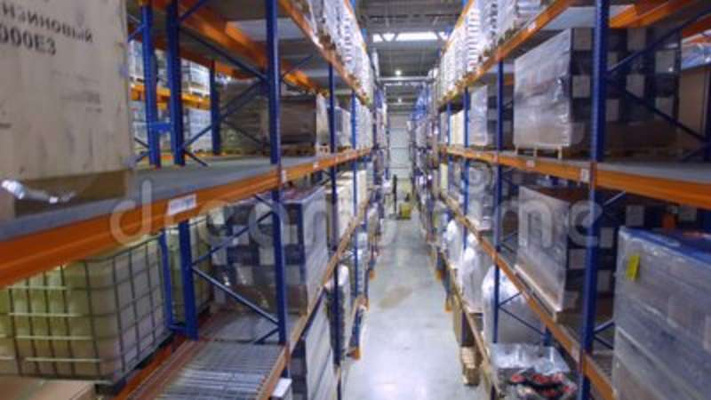 A long warehouse aisle with a forklift in the distance