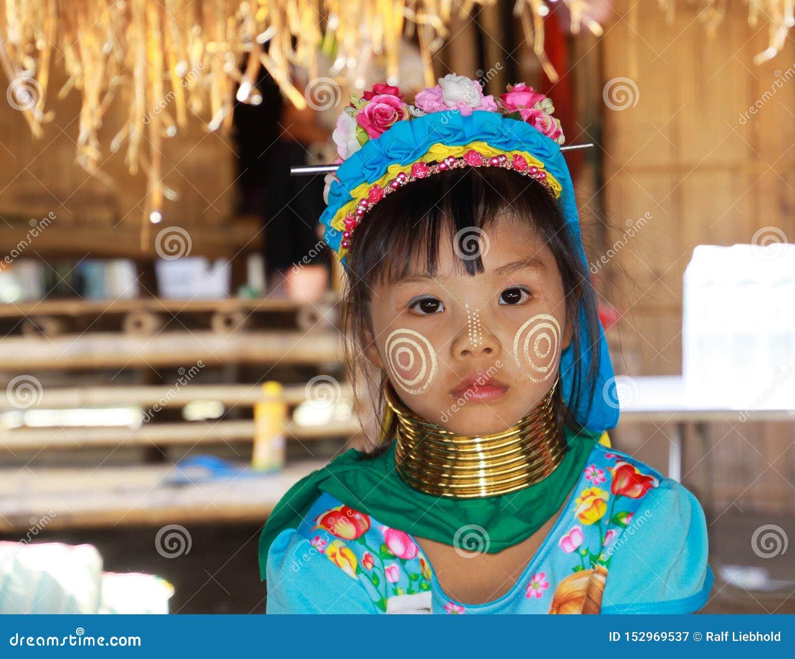 LONGNECK HET DORP VAN KAREN, THAILAND - DECEMBER 17 2017: Sluit omhoog portret van jong lang halsmeisje met Thanaka-gezicht het s