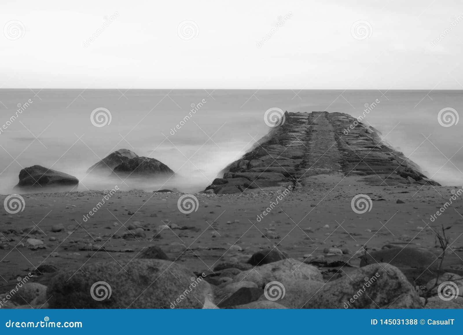 Longo-exposição sonhadora em preto e branco, de uma praia rochosa e de um molhe que apontam para o horizonte, ilha de bloco, RI