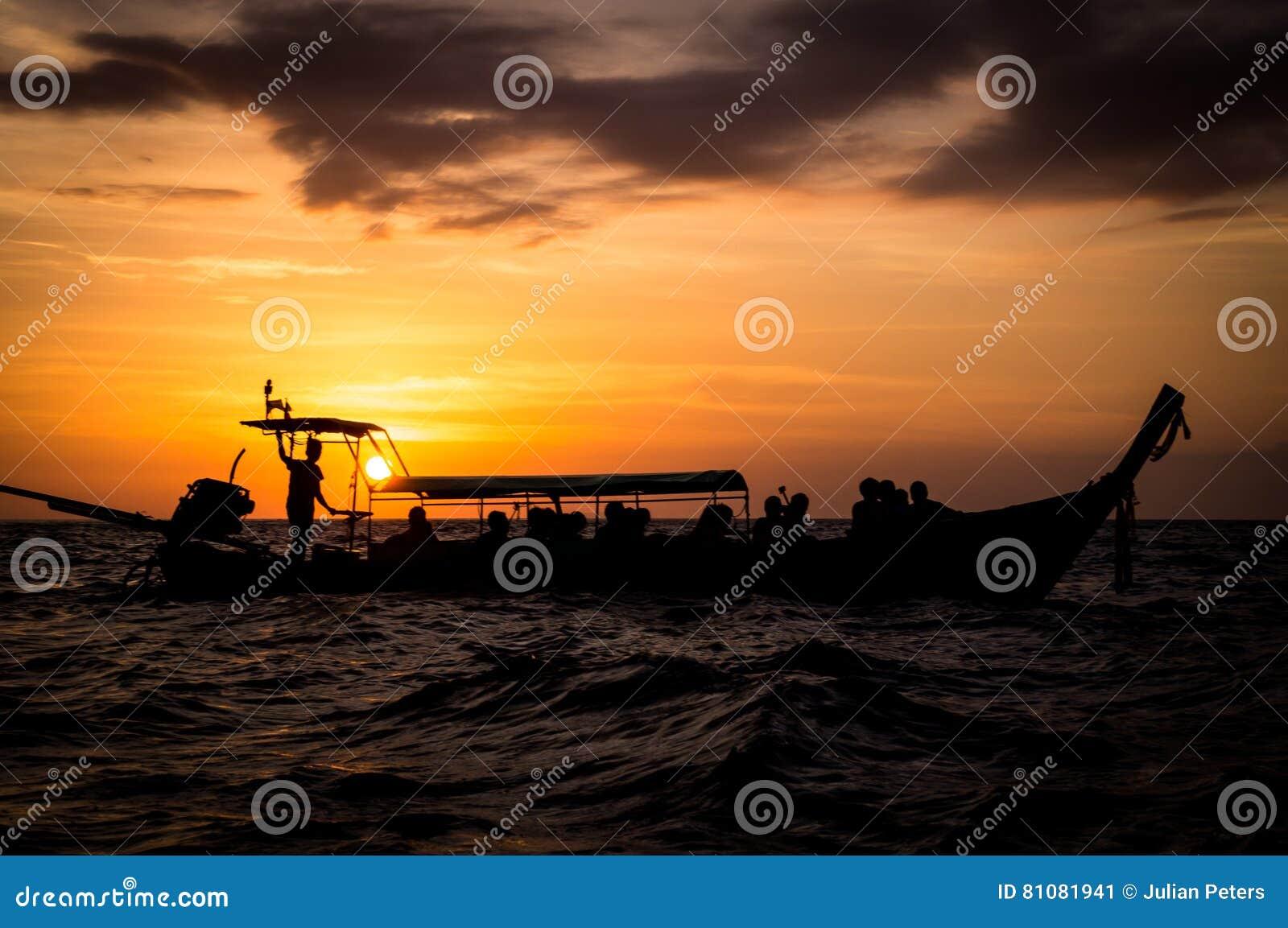 Longtail-Boot im Meer bei Sonnenuntergang in Thailand
