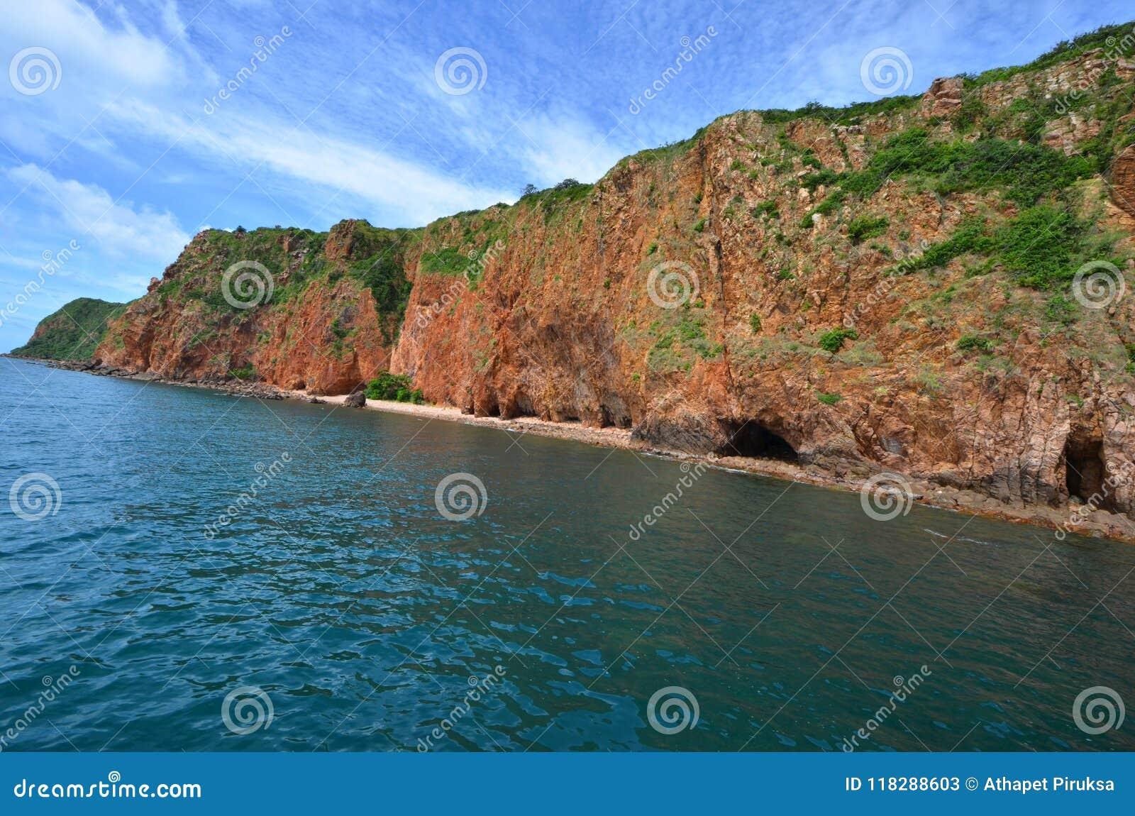 Longue île de roche avec l arbre vert en mer bleue