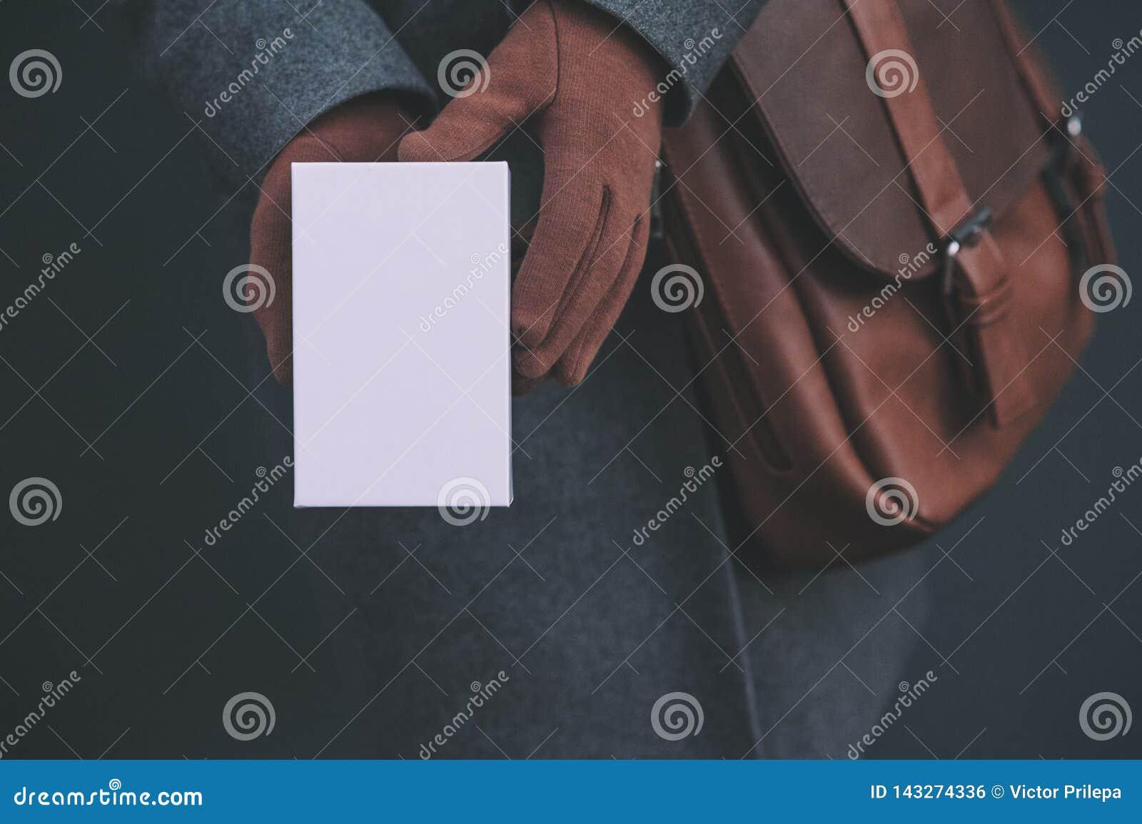 Longue bannière avec la moquerie vers le haut d un boîtier blanc d un smartphone La fille dans un manteau et des gants bruns tien