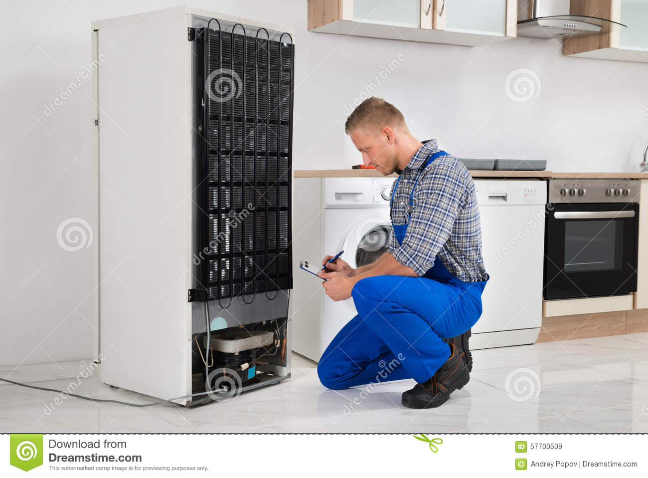 Loodgieter Writing On Clipboard in Front Of Refrigerator