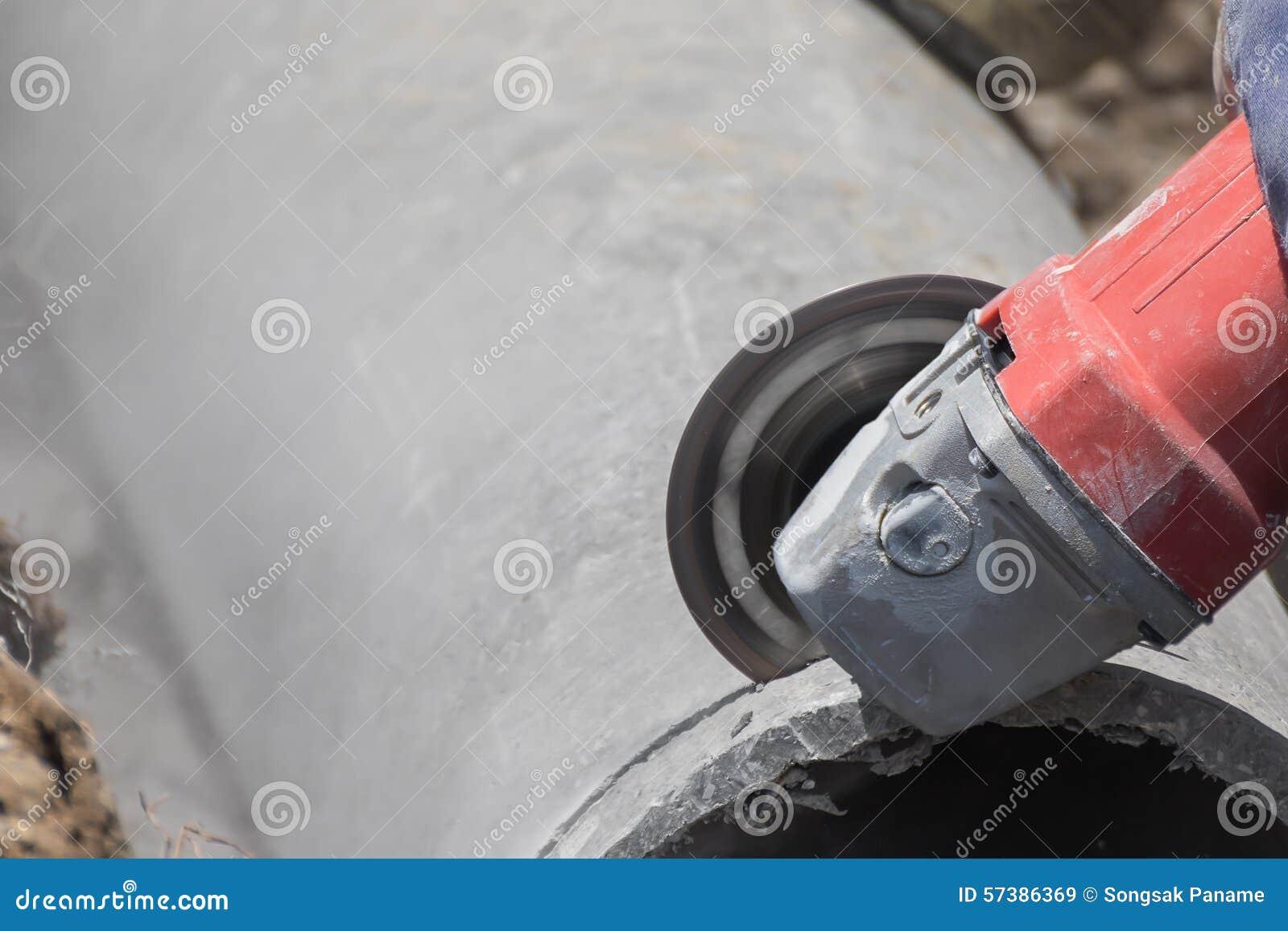 Loodgieters die concrete waterpijpen snijden