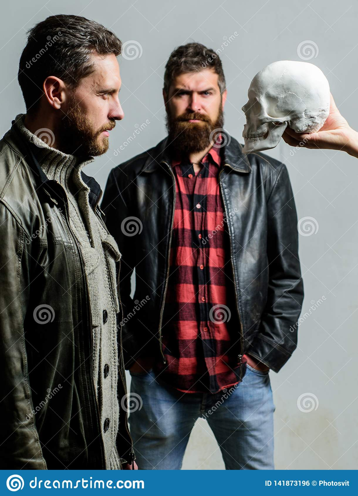 Looking deep into eyes of your fear. Man brutal bearded hipster looking at skull symbol of death. Overcome your fears