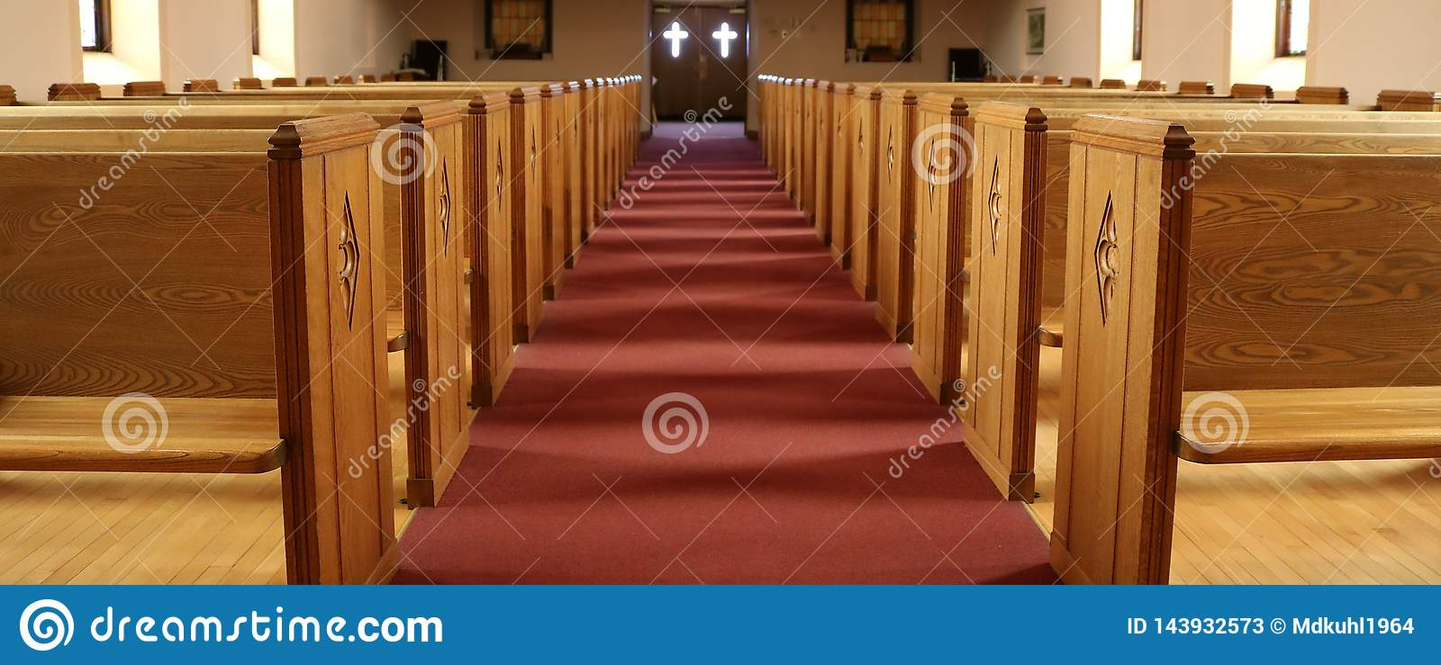 Aisle of traditional Christian church with empty pews