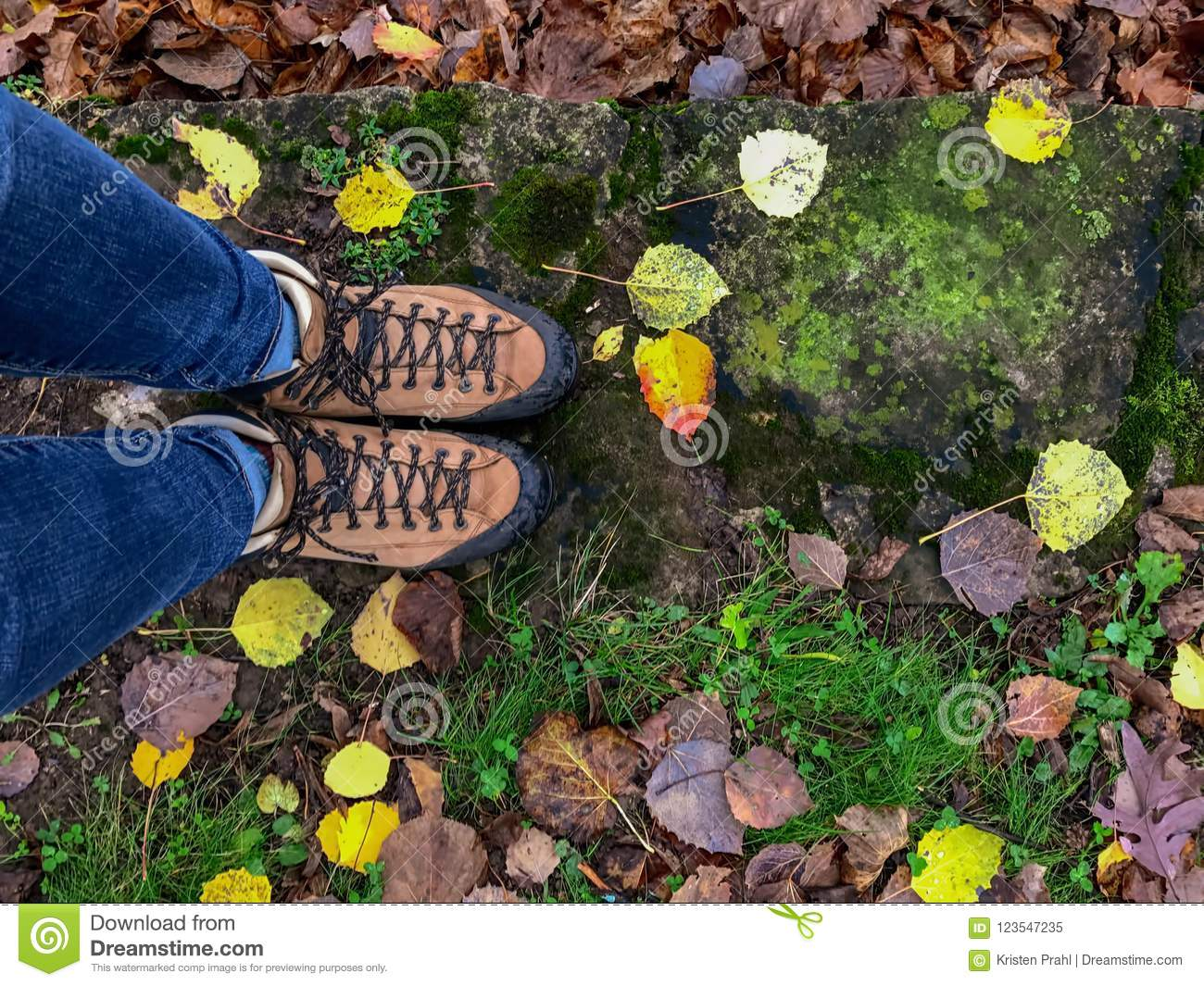 Looking down at woman`s feet in hiking boots on a rainy colorful