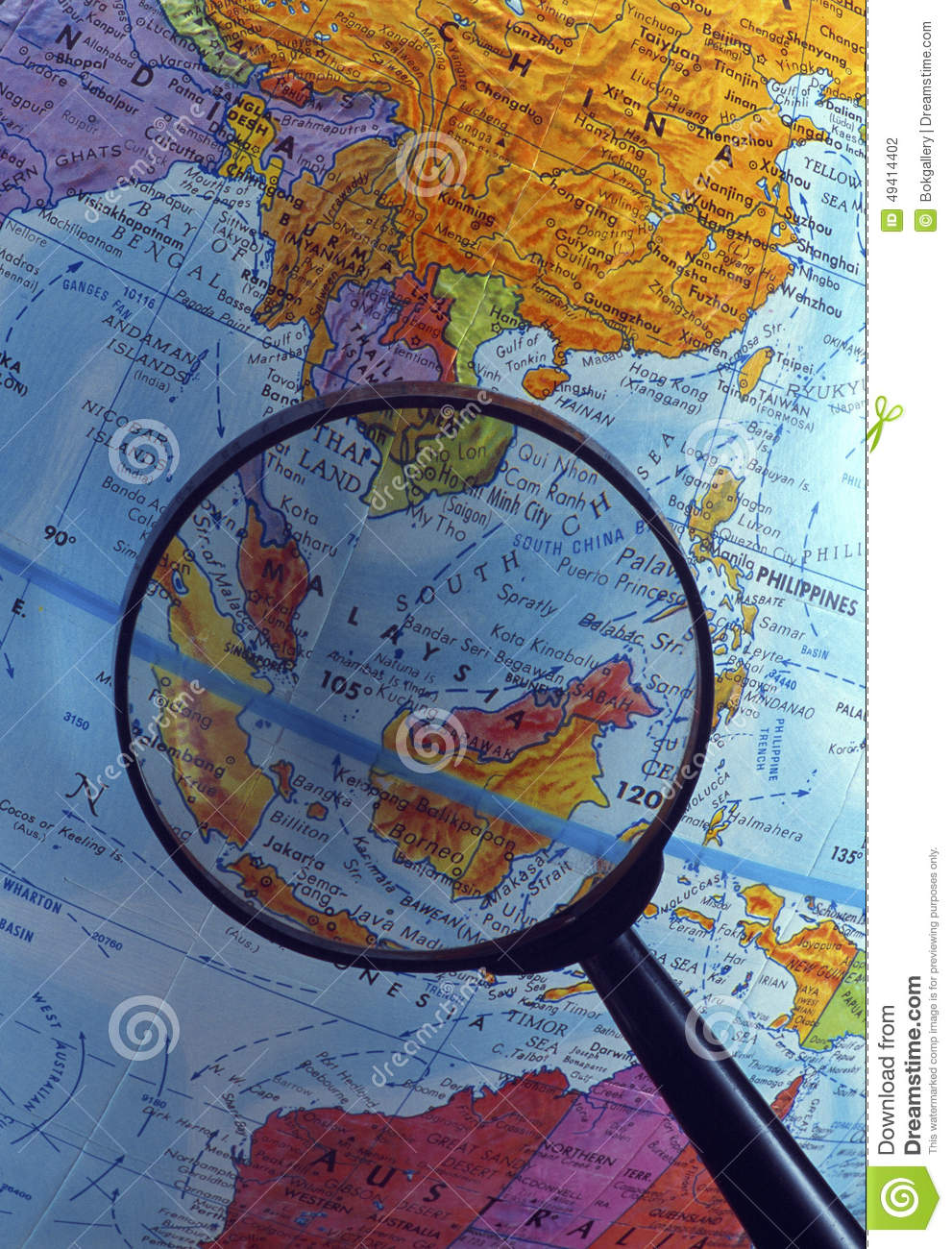 Looking at globe using magnifying glass (South East Asian Region)