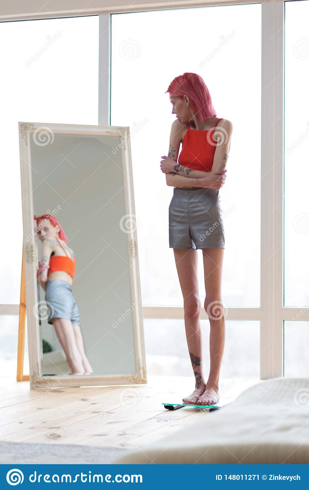 Skinny Unhealthy Woman Wearing Shorts And Top Looking Into