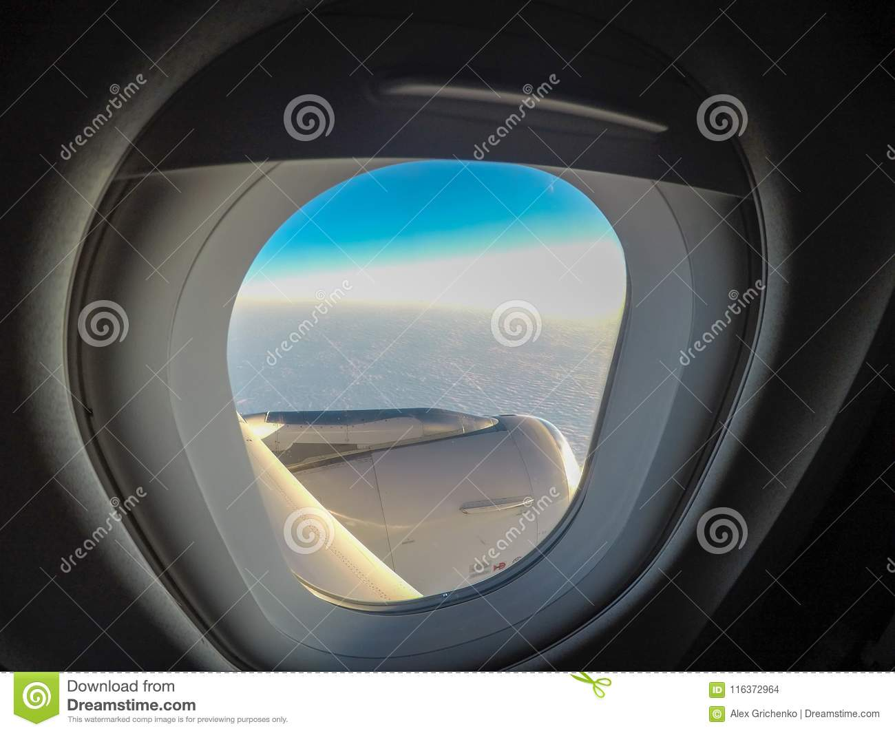 Looking Out Airplane Window And Flying Above The Clouds Stock Photo