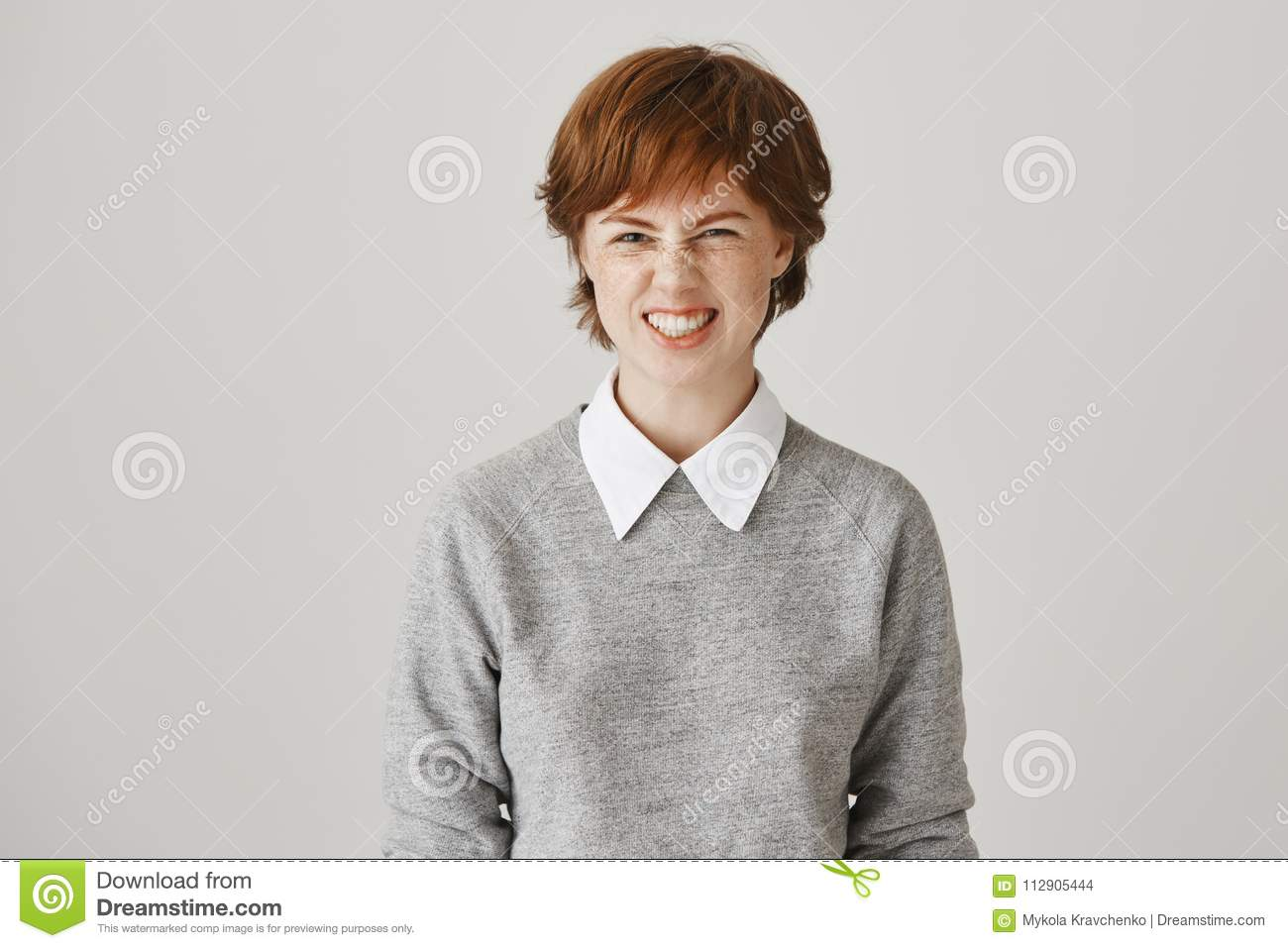 Looking sassy today. Studio portrait of attractive emotive redhead woman  with cute freckles squinting and