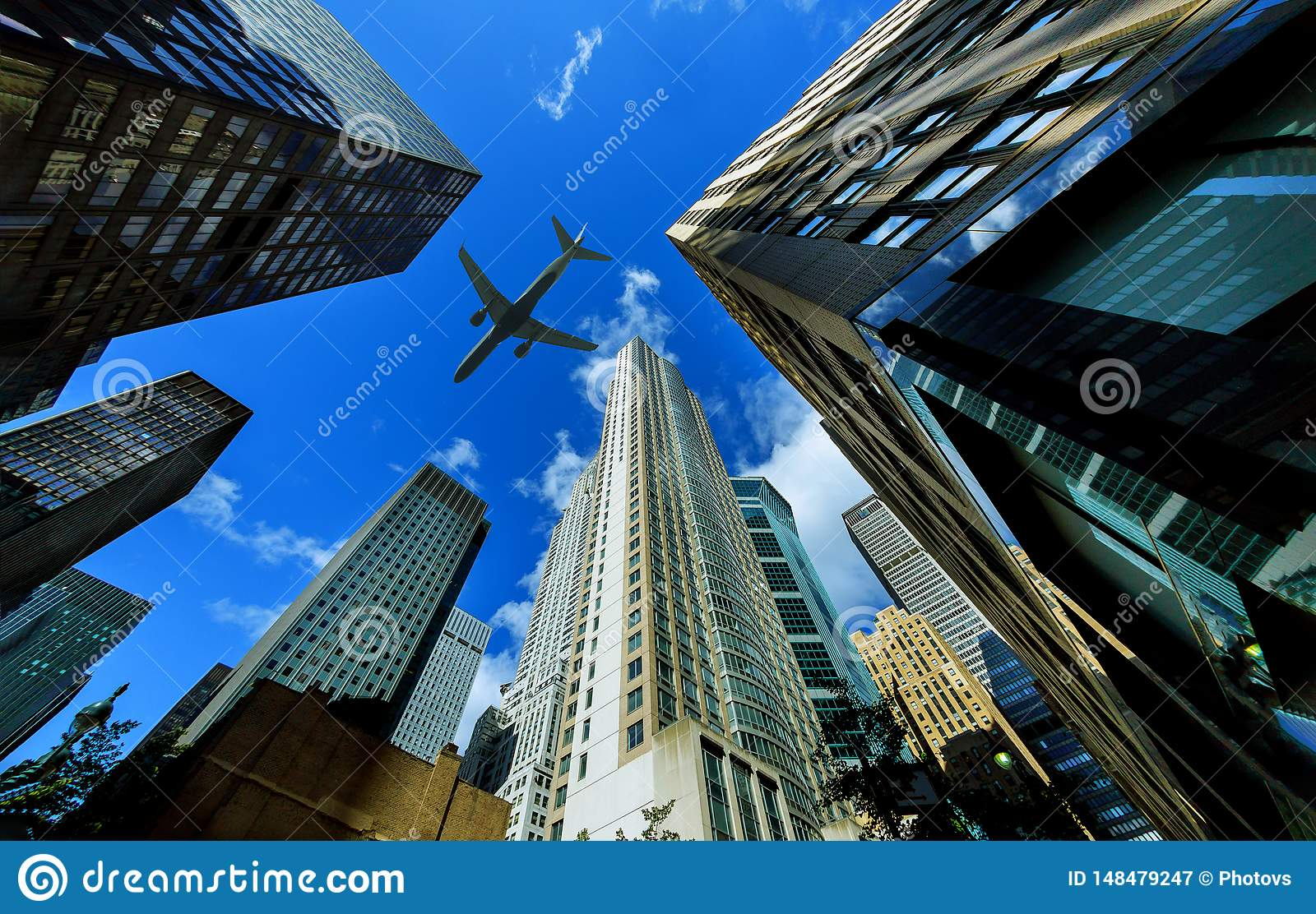 Looking up at New York city skyscrapers in financial district, NYC USA plane flying