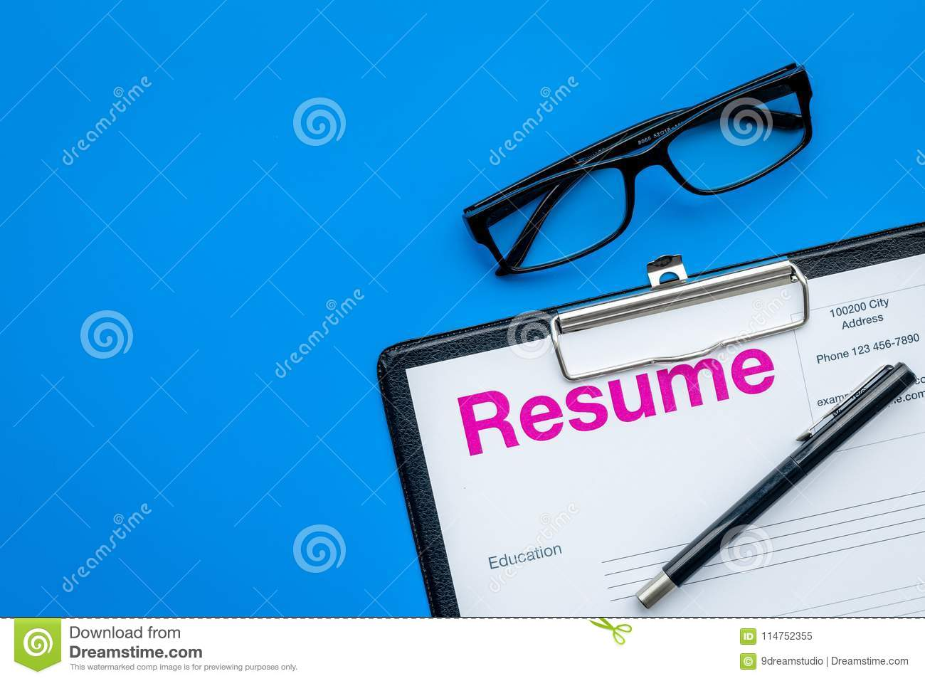 looking for work concept resume on pad near pen and glasses on blue