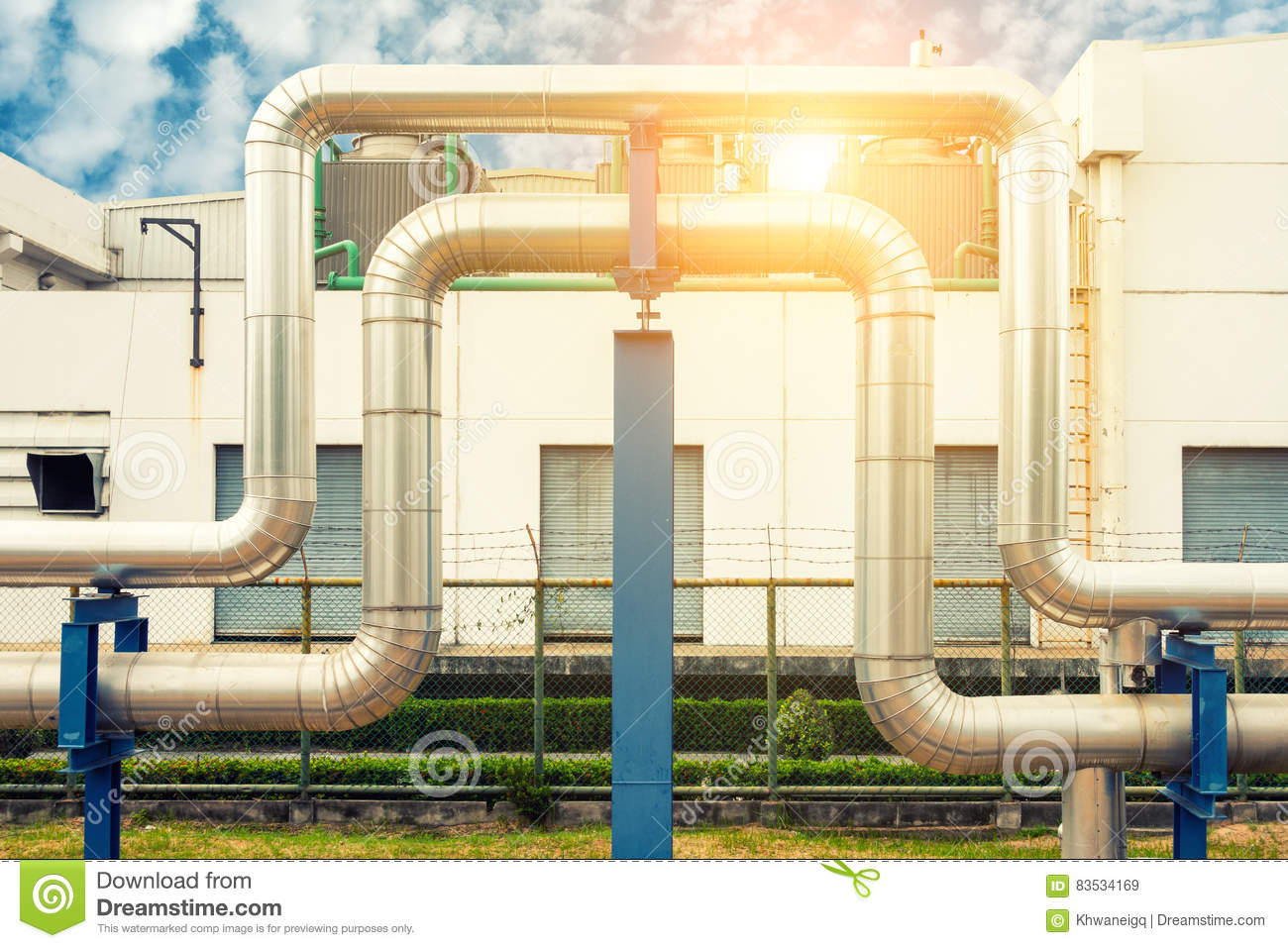 Loop steam pipeline on cooling tower background and sunshine., Insulation pipe.