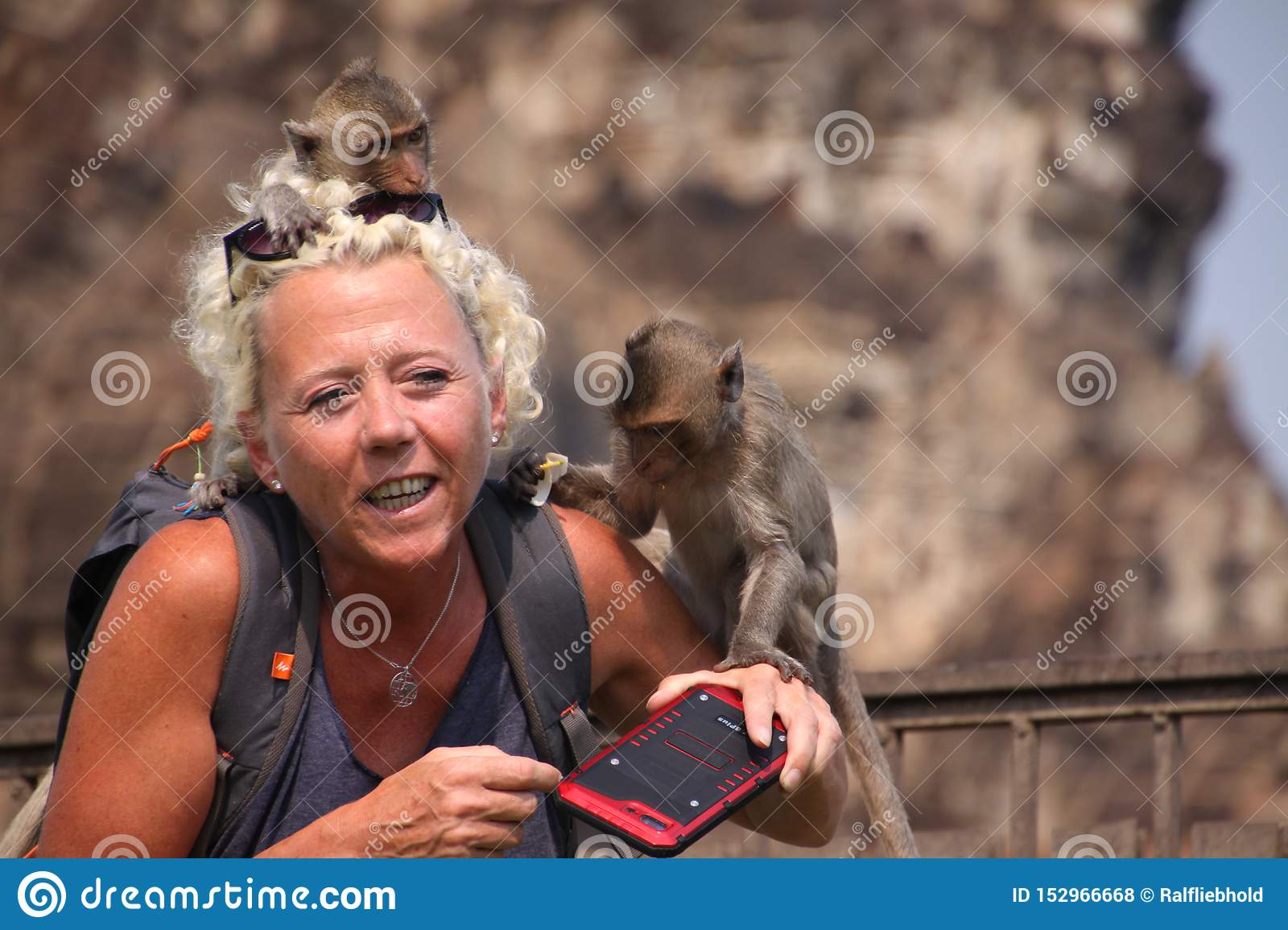 LOPBURI, THAILAND - JANUARY 9 2019: Tourist Woman attacked by monkeys stealing her sunglasses