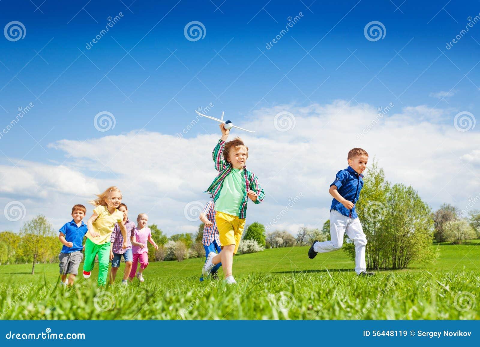 Lopende jongen met vliegtuigstuk speelgoed en andere kinderen